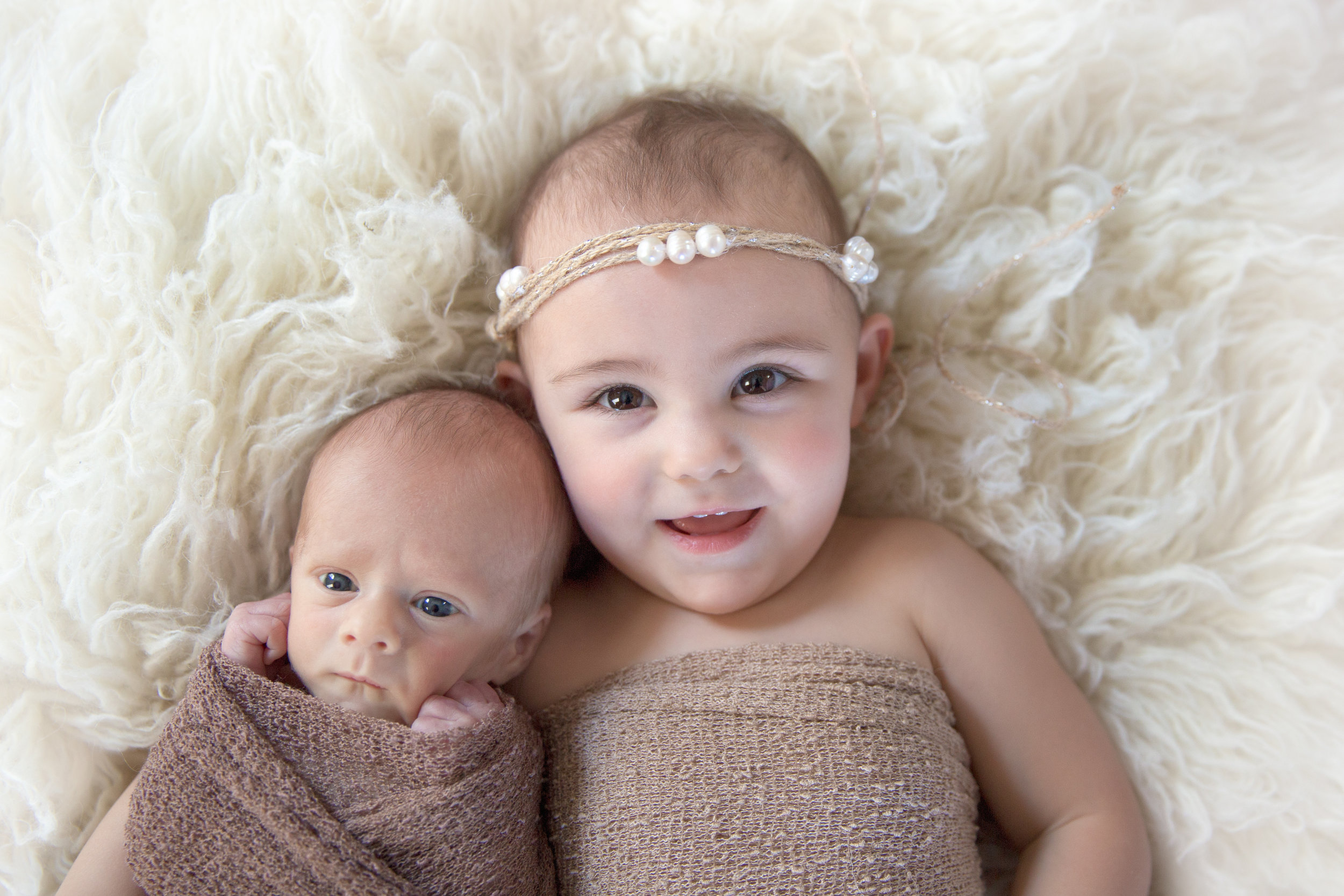 Siblings on a beanbag. A newborn baby boy and his sister. Calgary Newborn Photographer