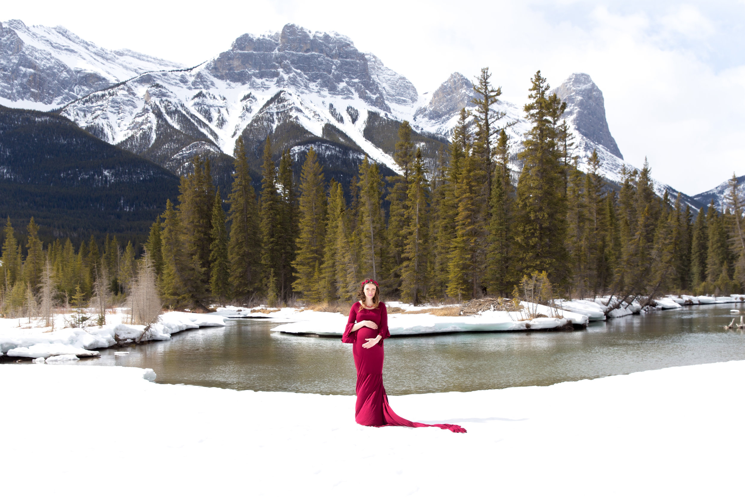 Mountain Maternity photoshoot in Alberta, Canada. Mother to be in a red gown on a white snow.