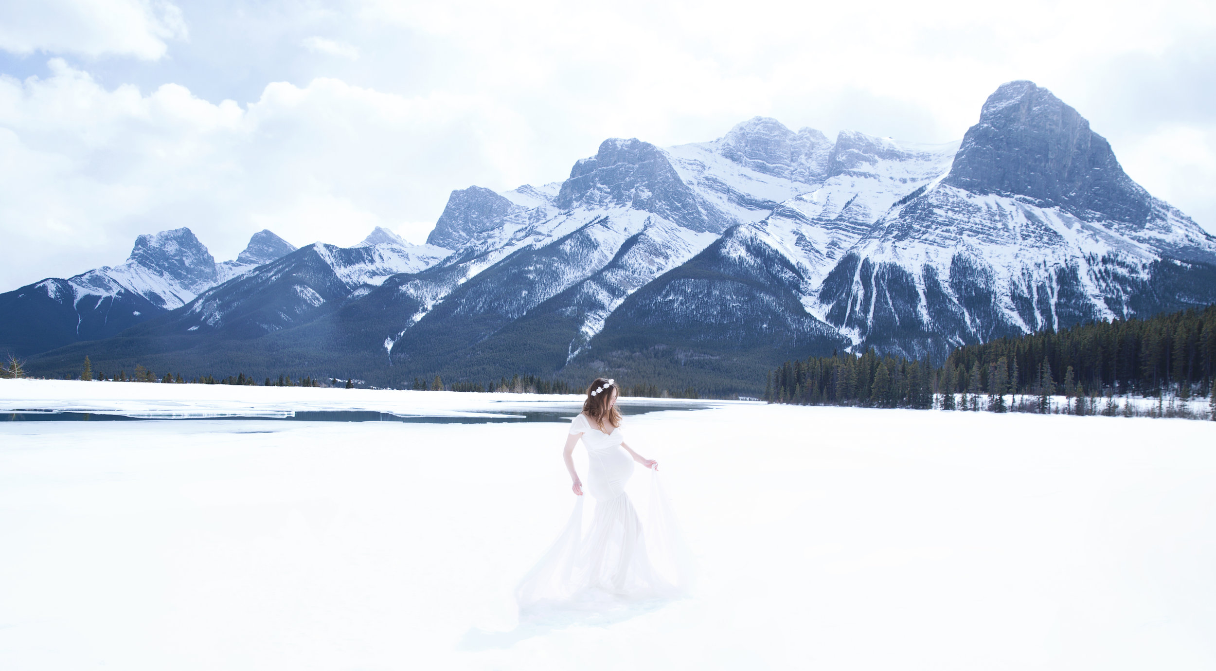 Winter mountain maternity session in Kananaskis Country. Mother-to-be in a white gown. Alberta photographer.