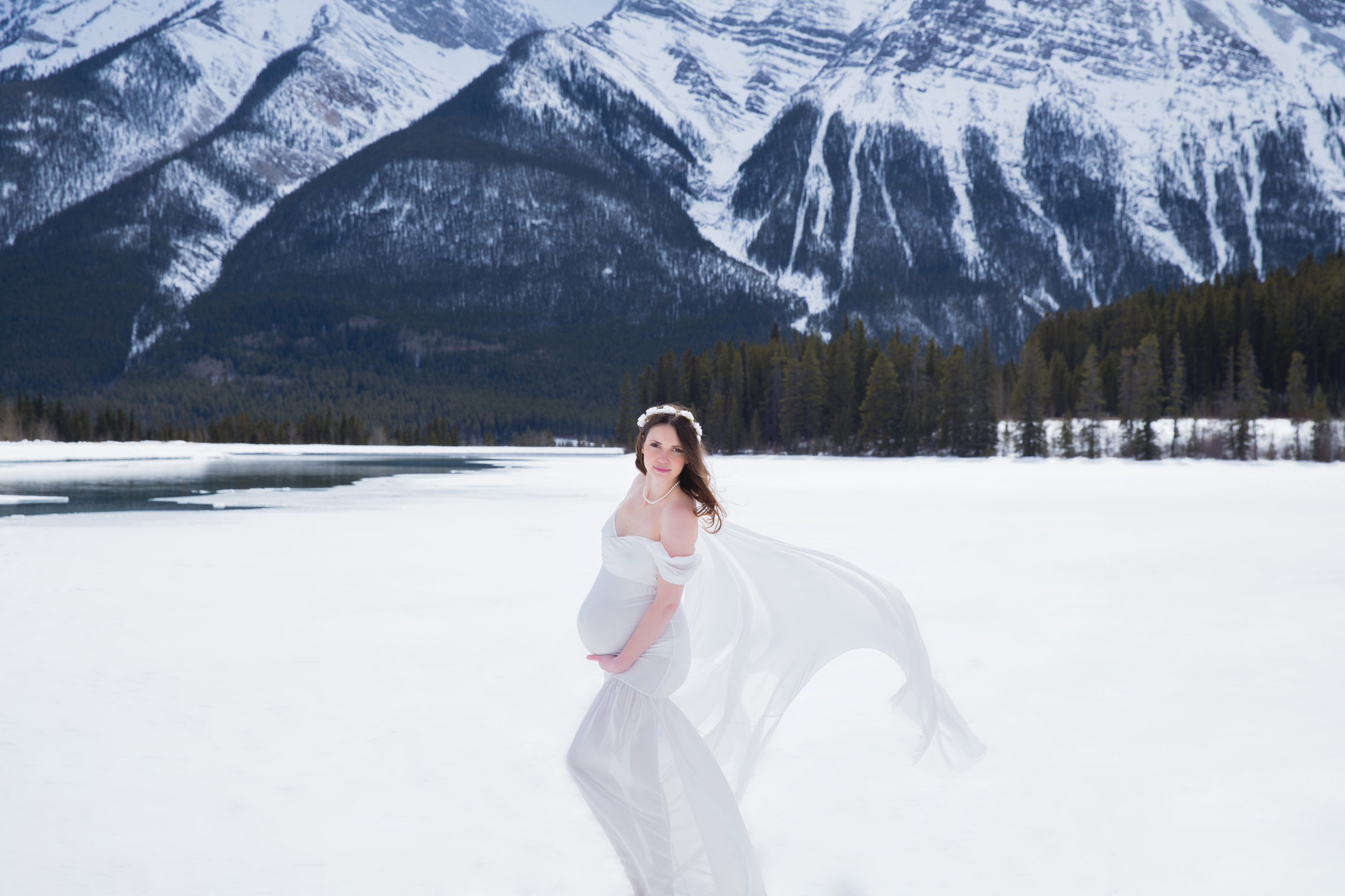 Mountain Maternity session during winter. Beautiful mother-to-be wearing a white gown on a snow in the mountains. Calgary and Airdrie photographer.