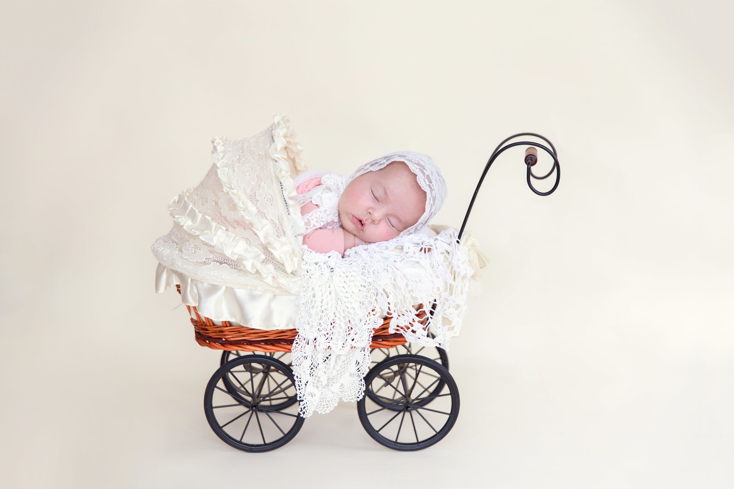 Newborn baby girl in a cute little stroller. Airdrie and Calgary Newborn Photographer