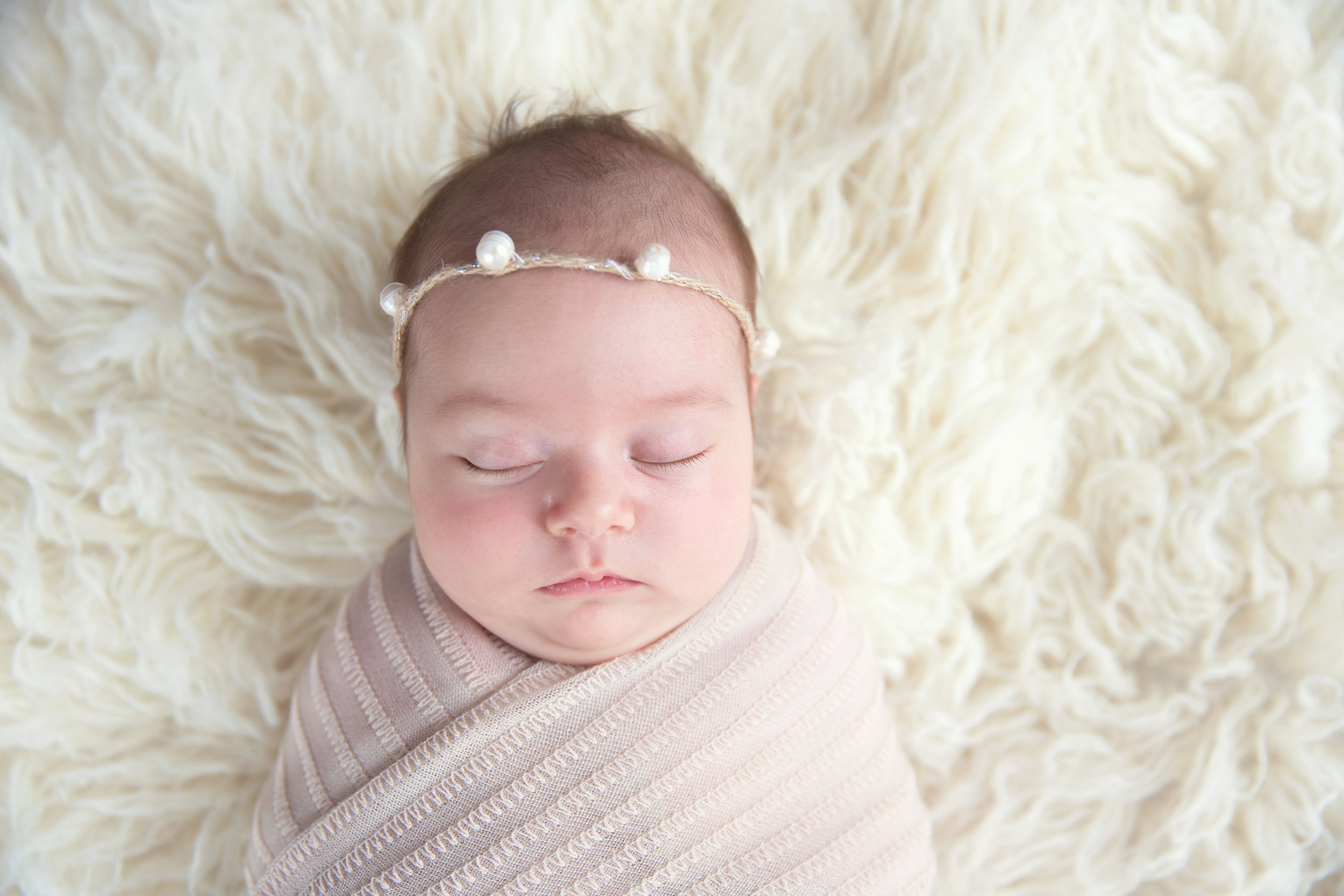 Newborn baby girl all wrapped up with a pearl headband. Newborn photographer in Airdrie, Alberta.