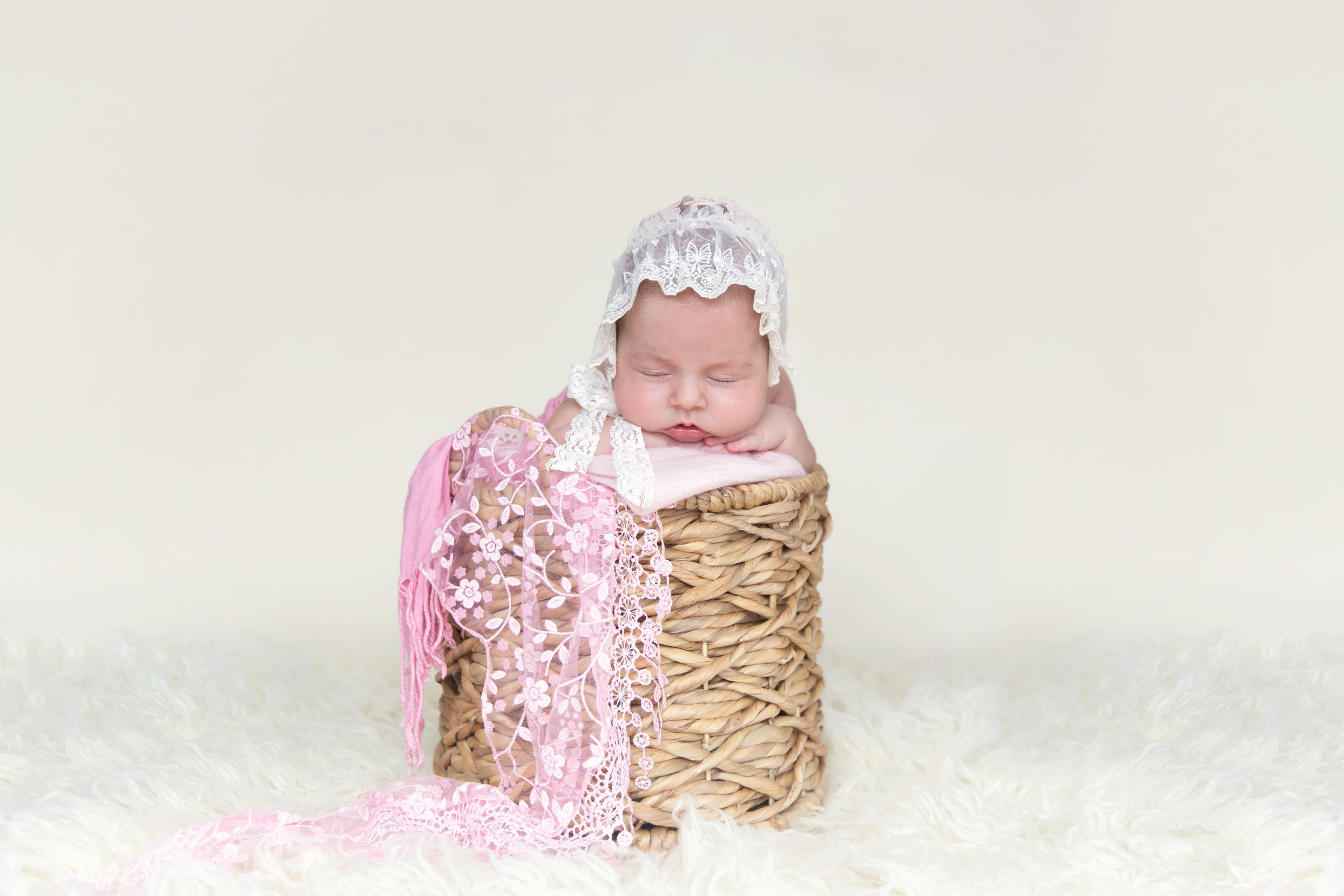 Baby girl in pink in a basket for her newborn photoshoot. Calgary and Airdrie Newborn Photographer.