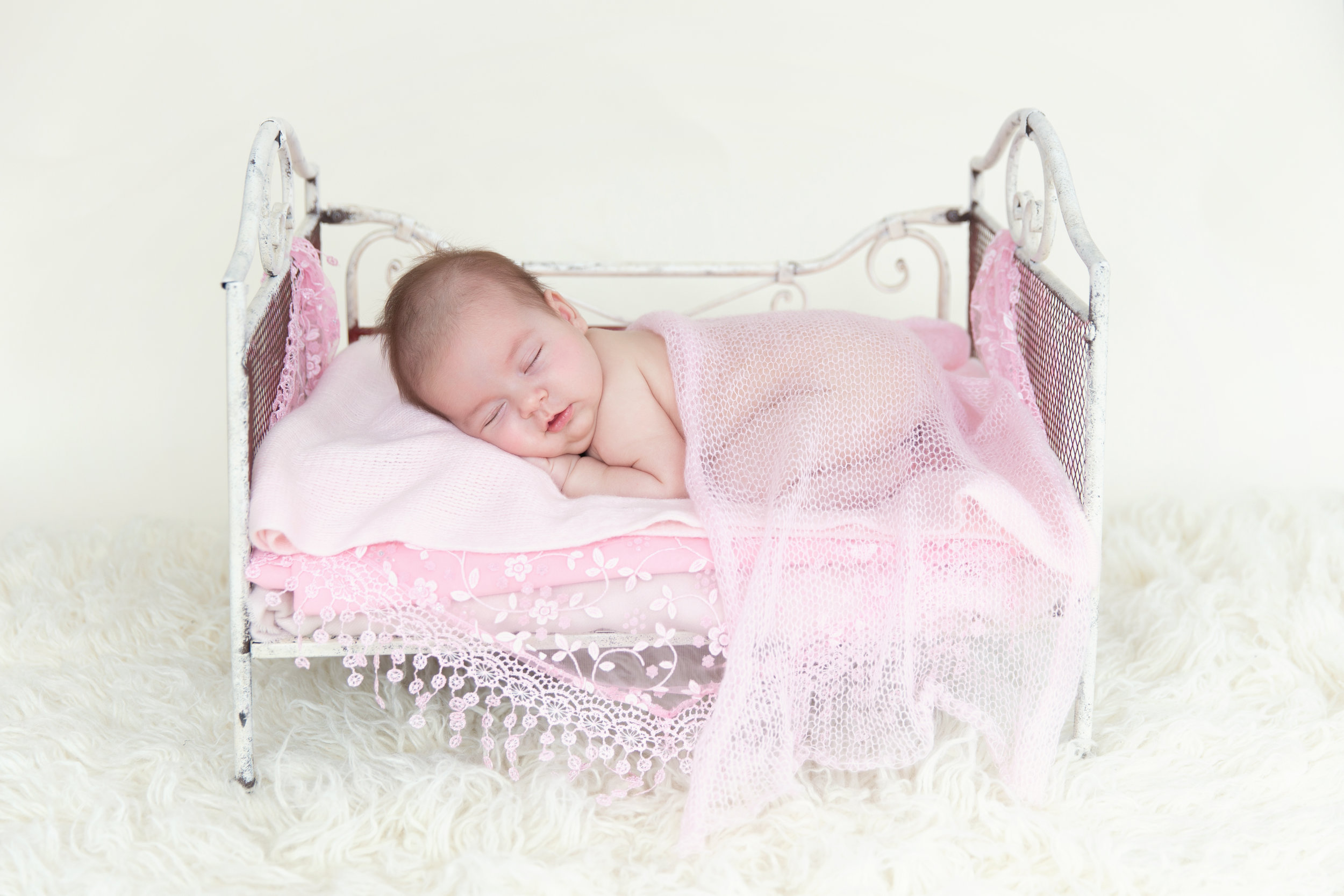 Newborn baby girl, smiling in her sleep, lying on an antique bed prop. Calgary and Airdrie Newborn Photographer.