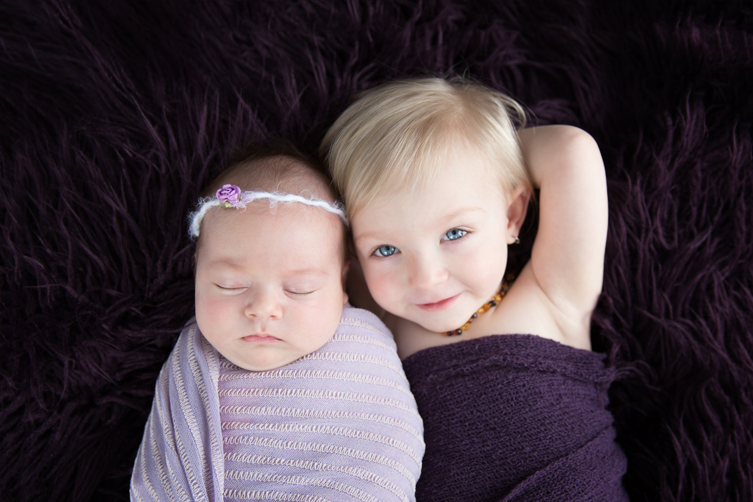 Two sisters in purple. Siblings shot on a beanbag. Newborn photographer in Calgary and Airdrie.