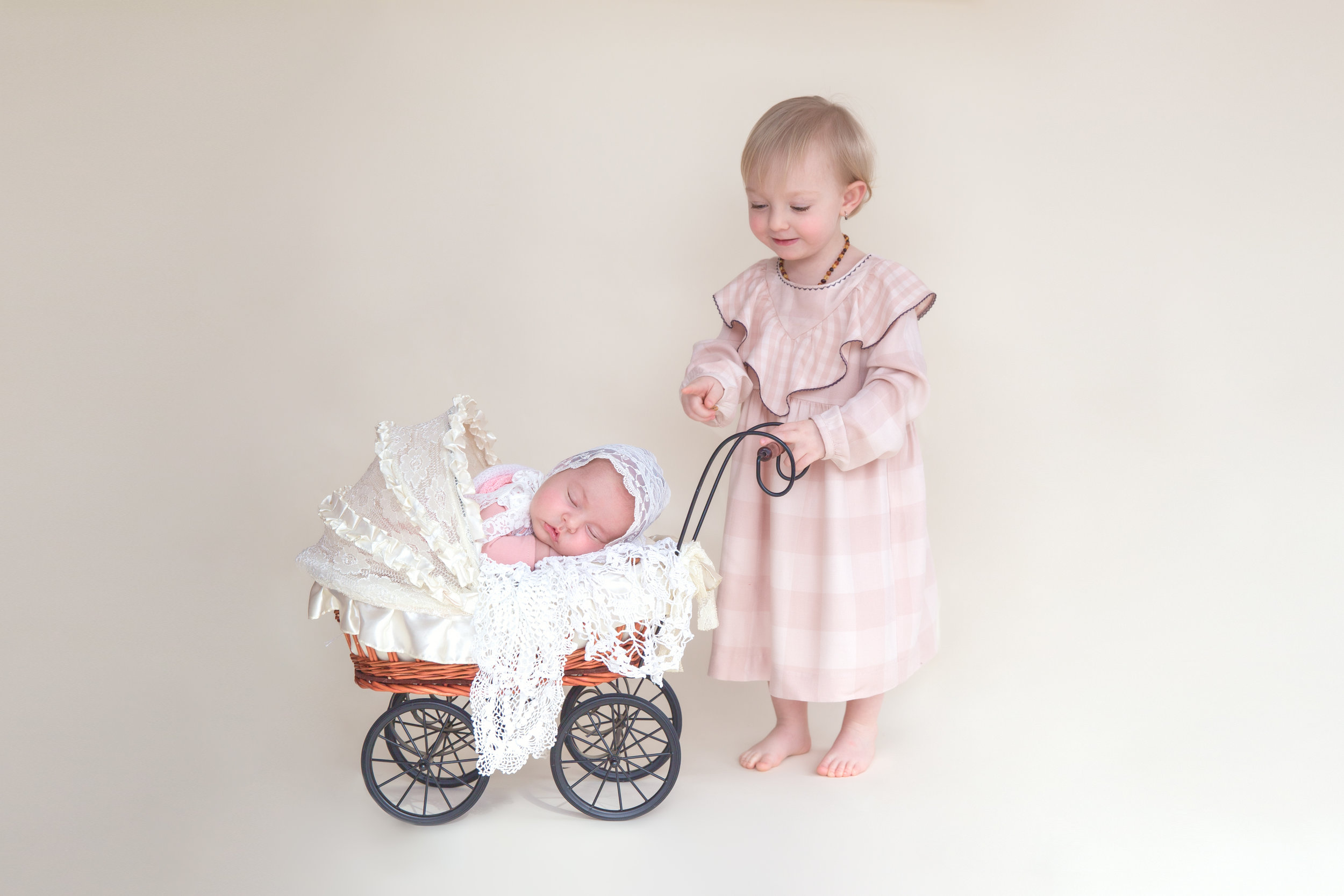 Sisters. Newborn baby girl in a stroller prop and her sister is pointing right at her. Calgary Newborn Photographer.