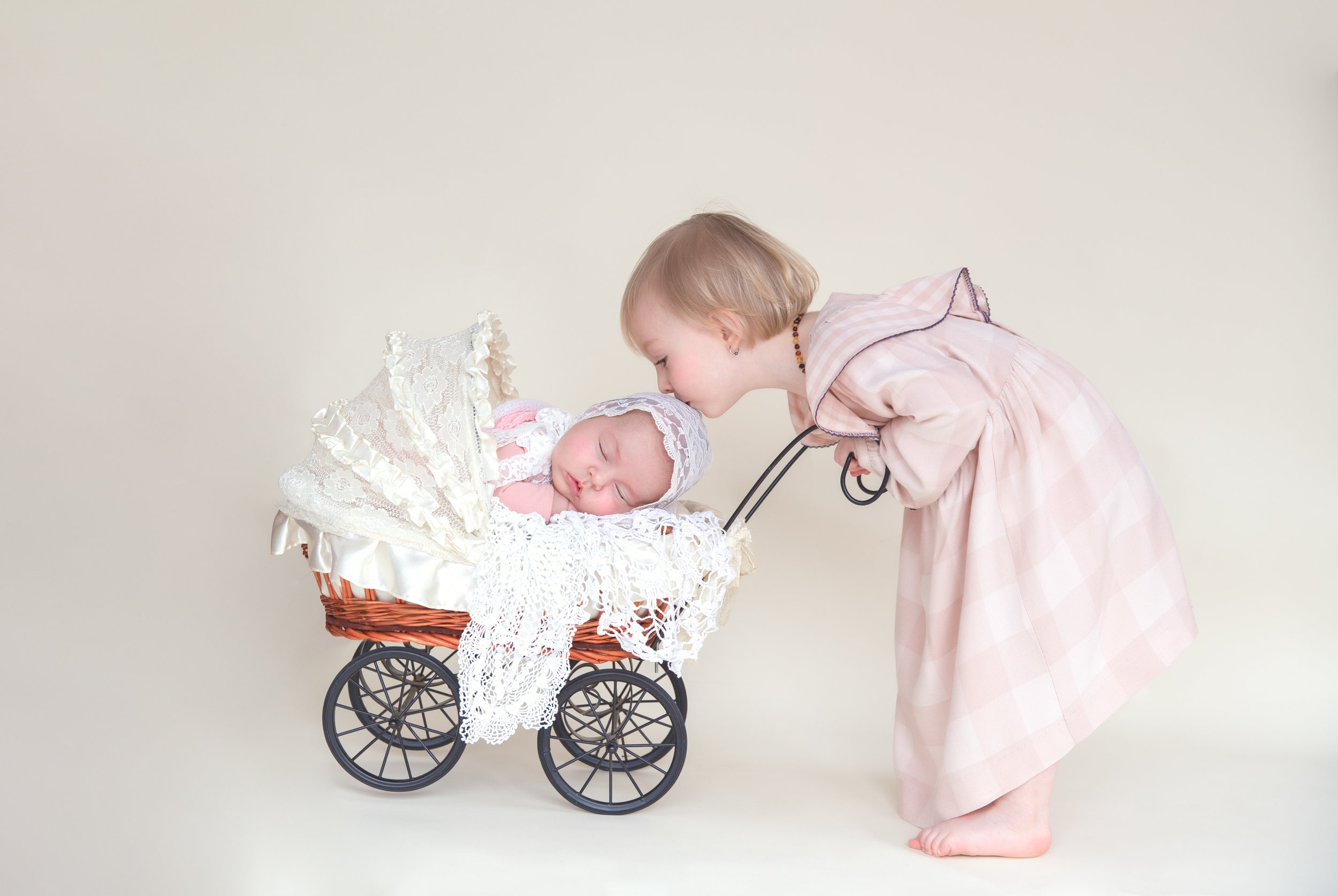 http://babyphotoawards.com/best-photography-gallery/37#photo_4781. Baby Photo Award winning picture of a newborn baby girl in a stroller and her sister kissing her on a head.