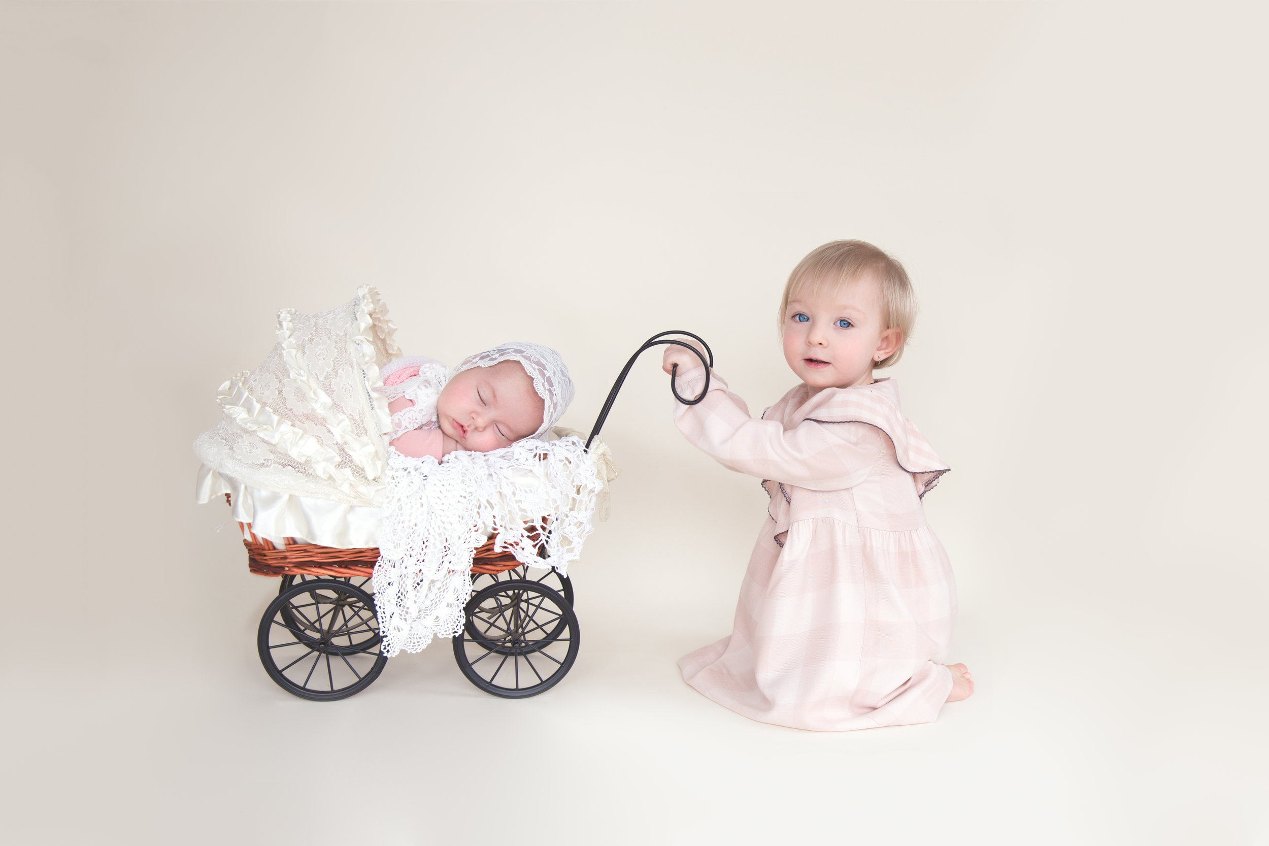 Baby girl in a stroller with her sister kneeling beside her. Newborn photographer in Calgary and Airdrie, Alberta.