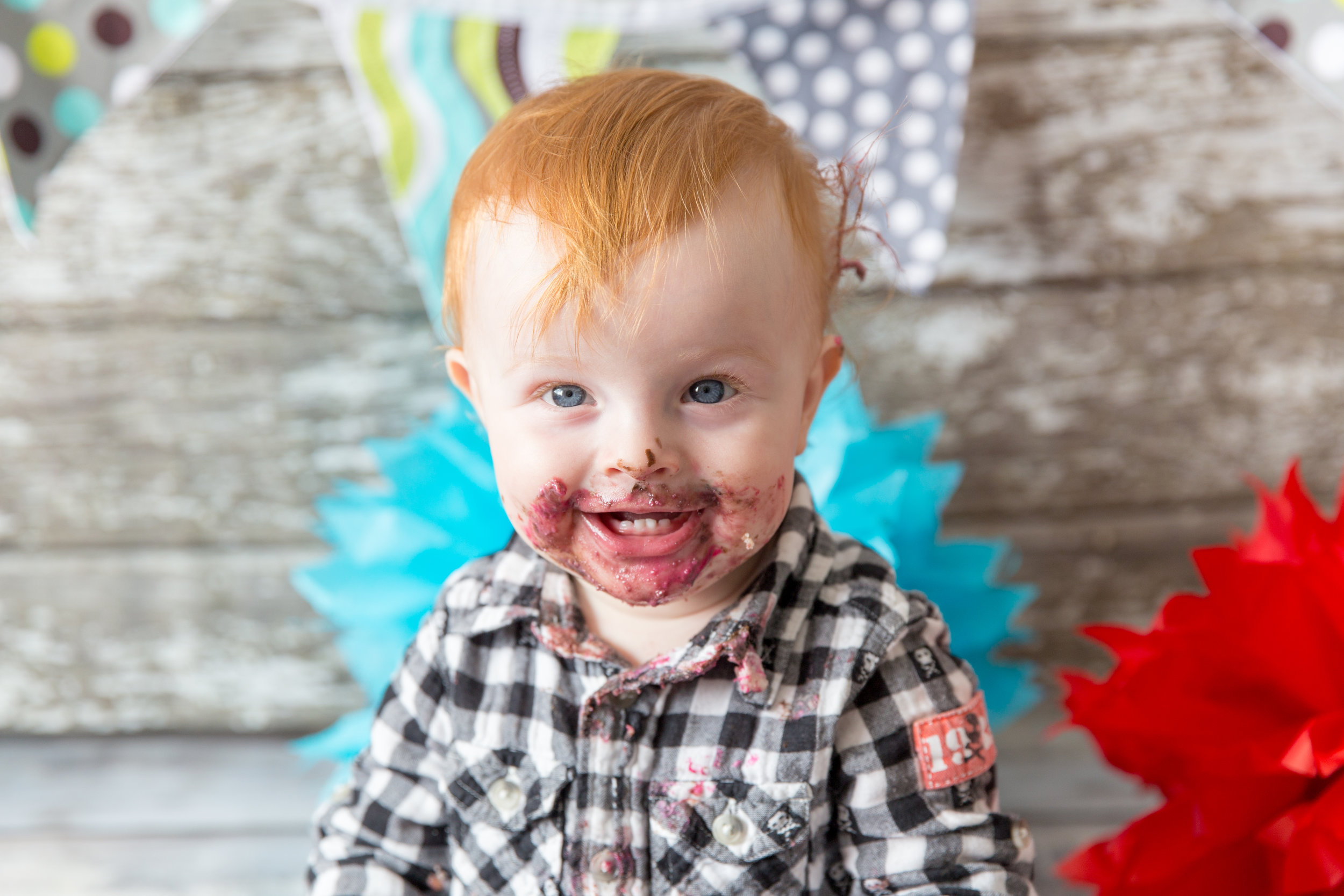 Baby boy with a face covered in cake. Successful cakesmash. Airdrie and Calgary Photographer.