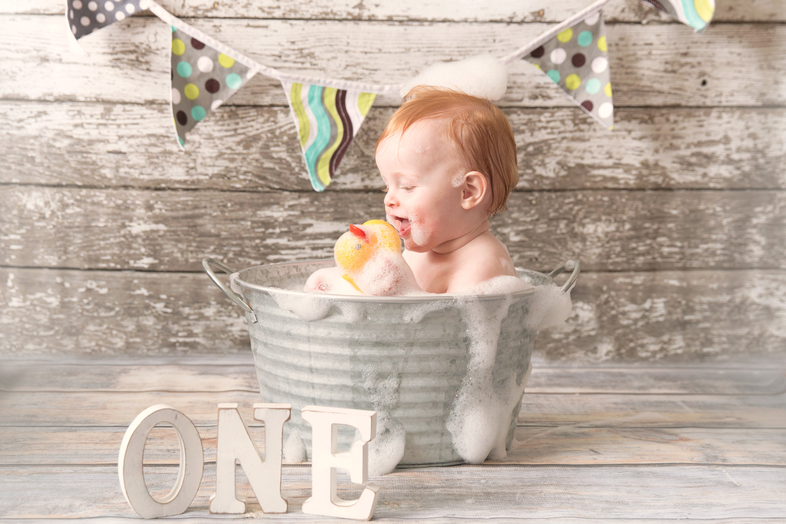 Baby boy enjoying a bubble bath after a successful cakesmash photoshoot. Calgary and Airdrie cakesmash photographer.