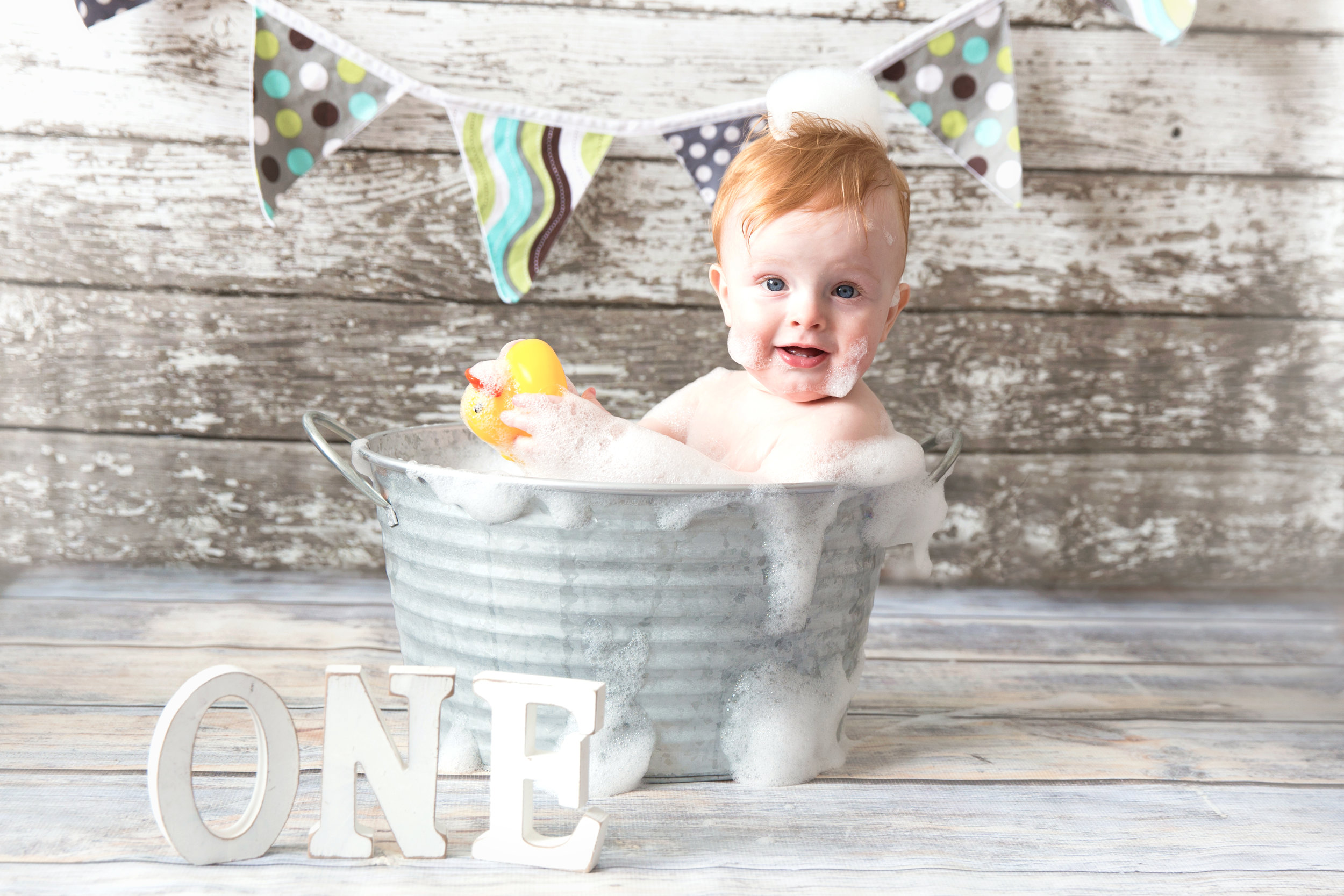 Baby boy is enjoying a bubble bath after smashing his cake. Calgary cakesmash photographer.