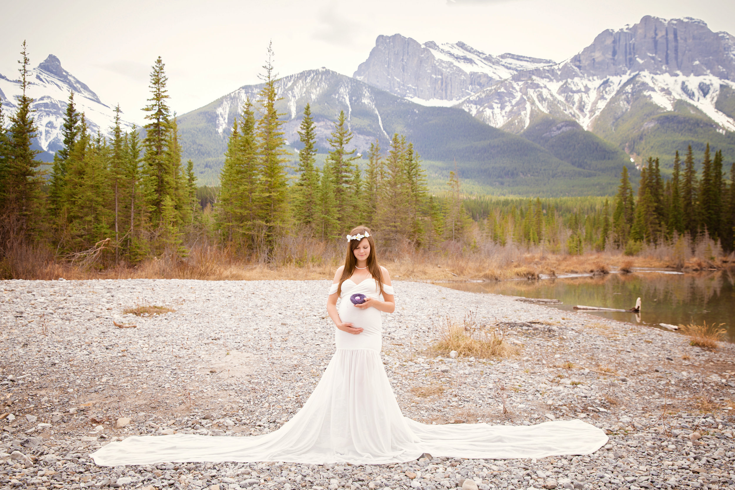 Beautiful mom-to-be in a white gown holding a nest. Mountain photoshoot in Canmore, Alberta. Milashka Photography