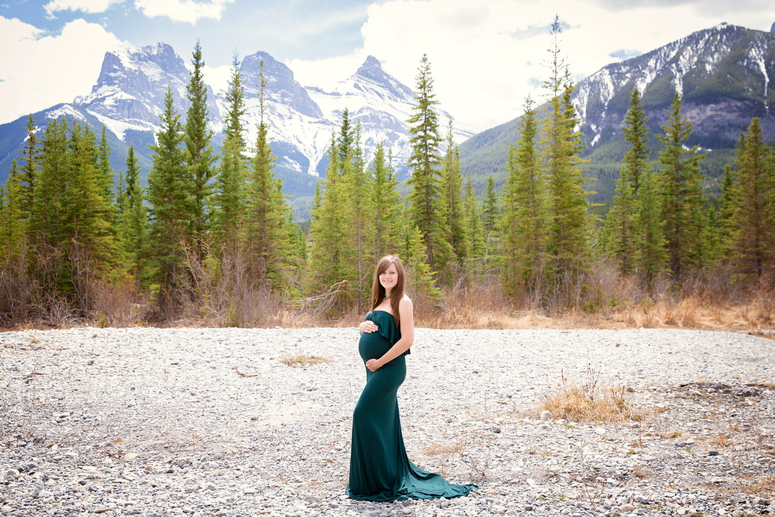 The Three Sisters Mountains in Canmore, Alberta. Faith, Charity and Hope. Beautiful mother-to-be in a green gown. Canmore maternity photographer. Milashka Photography
