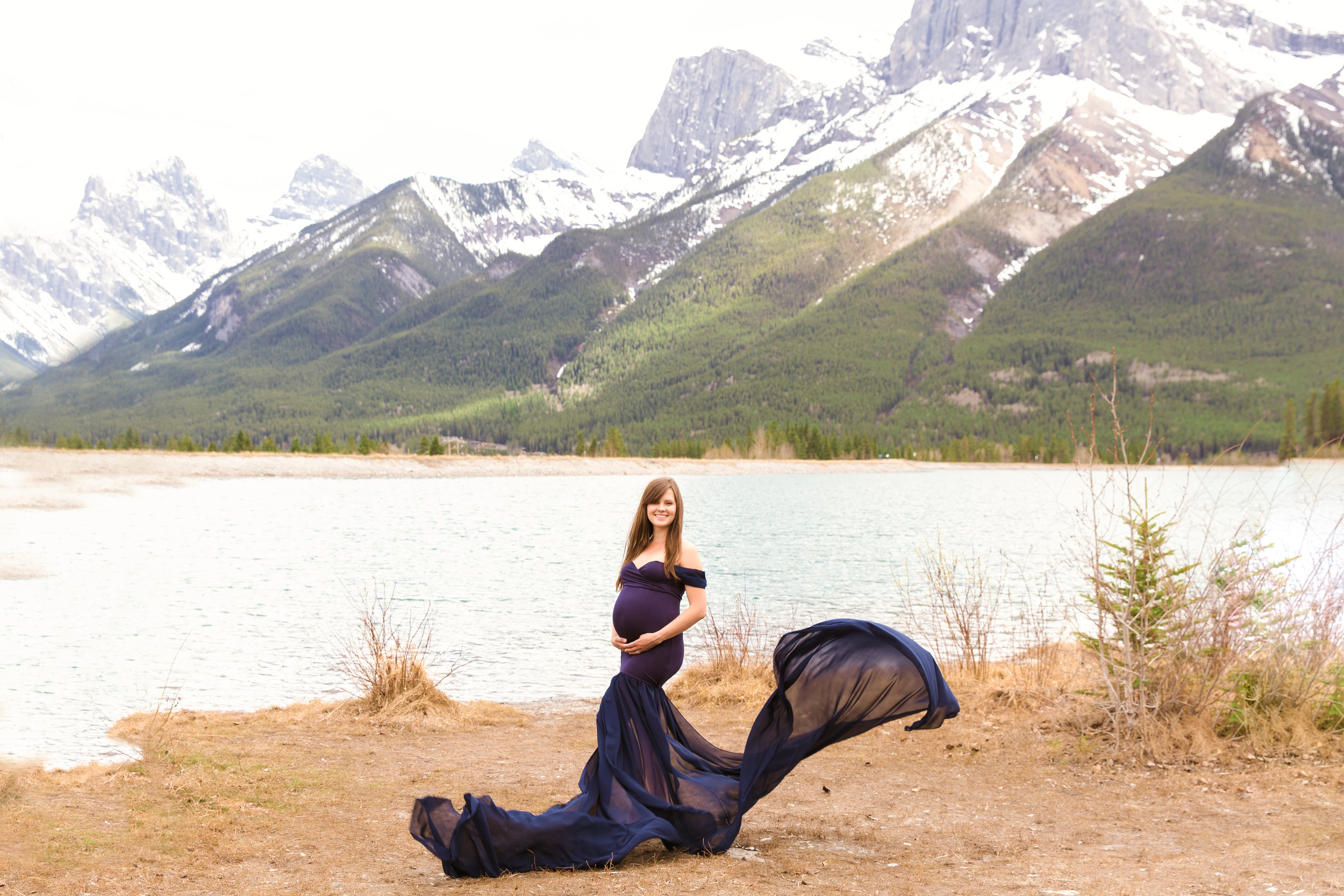Beautiful expectant mother in a gorgeous blue gown in the mountains. Canmore mountain maternity session. Milashka Photography.