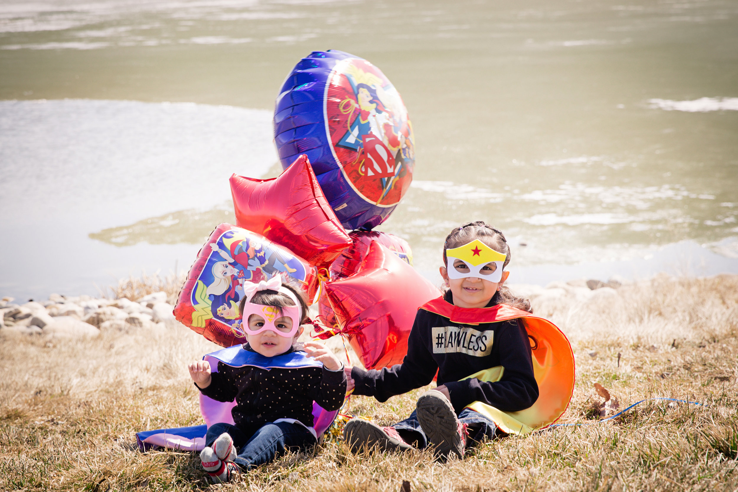 Two cute girls dressed as superheroes with balloons by the lake. Calgary family photographer. Milashka Photography.