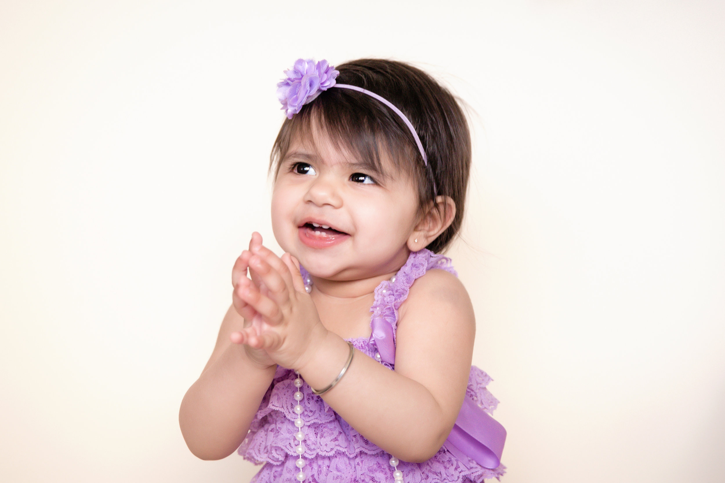 Sweet little girl, dressed in a purple romper clapping hands. Calgary and Airdrie baby photographer. Milashka photography