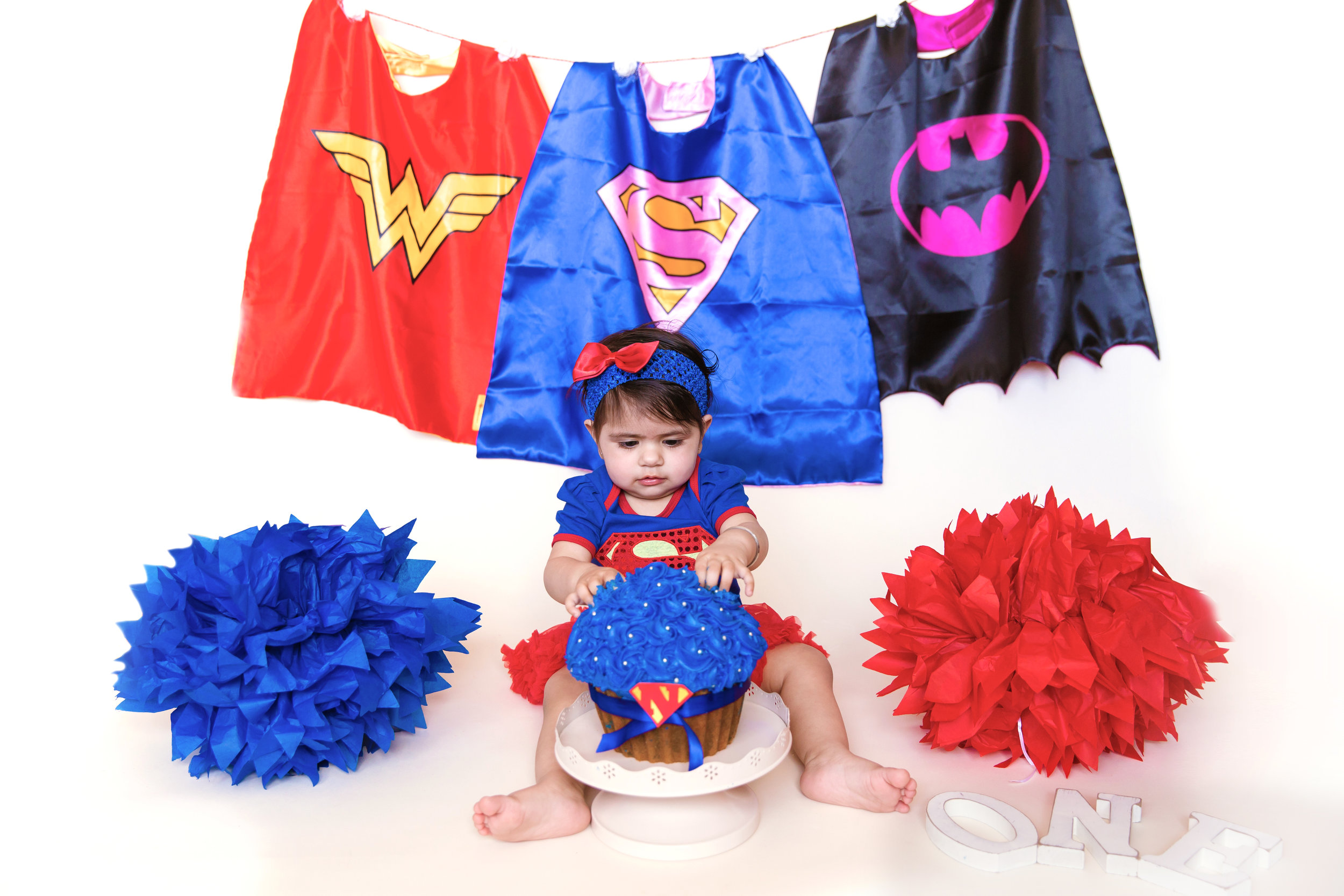 Superhero cakesmash photoshoot for a girl. Baby girl smashing her superhero cake. Calgary cakesmash photographer. Milashka Photography.