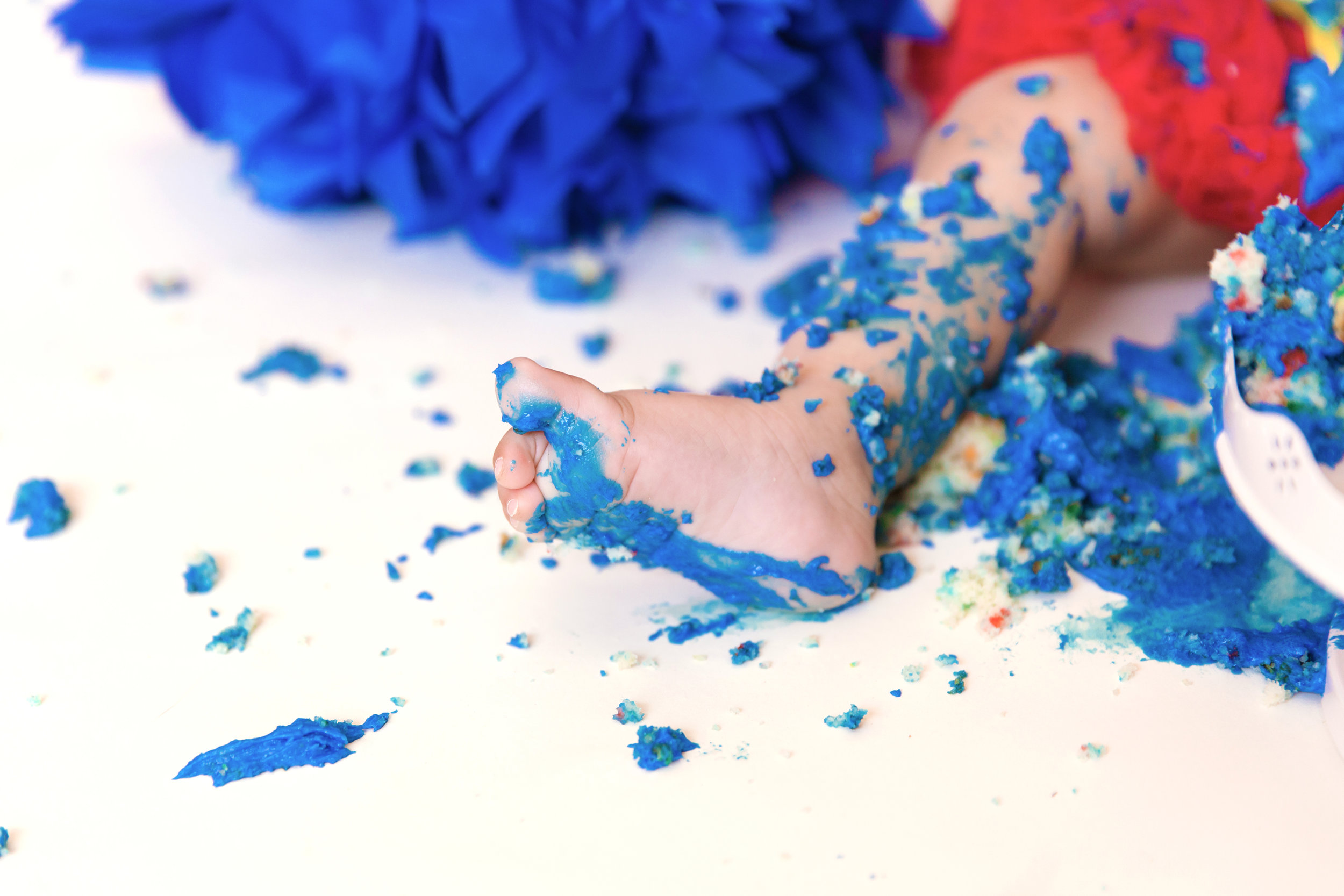 Little feet all covered in cake icing. Cakesmash photoshoot. Calgary photographer. Milashka photography
