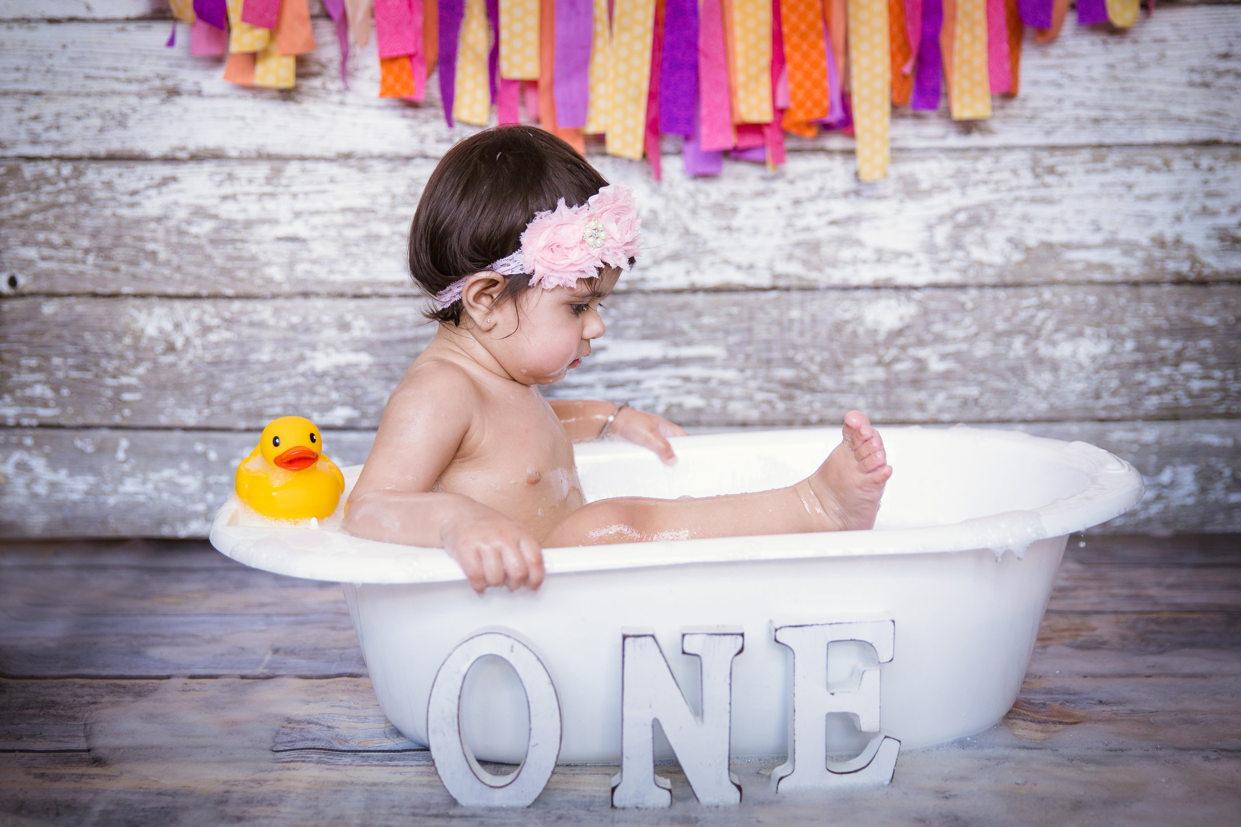 Baby girl looking at her foot in a bubble bath after a cakesmash. Milashka Photography - Calgary cakesmash photographer.