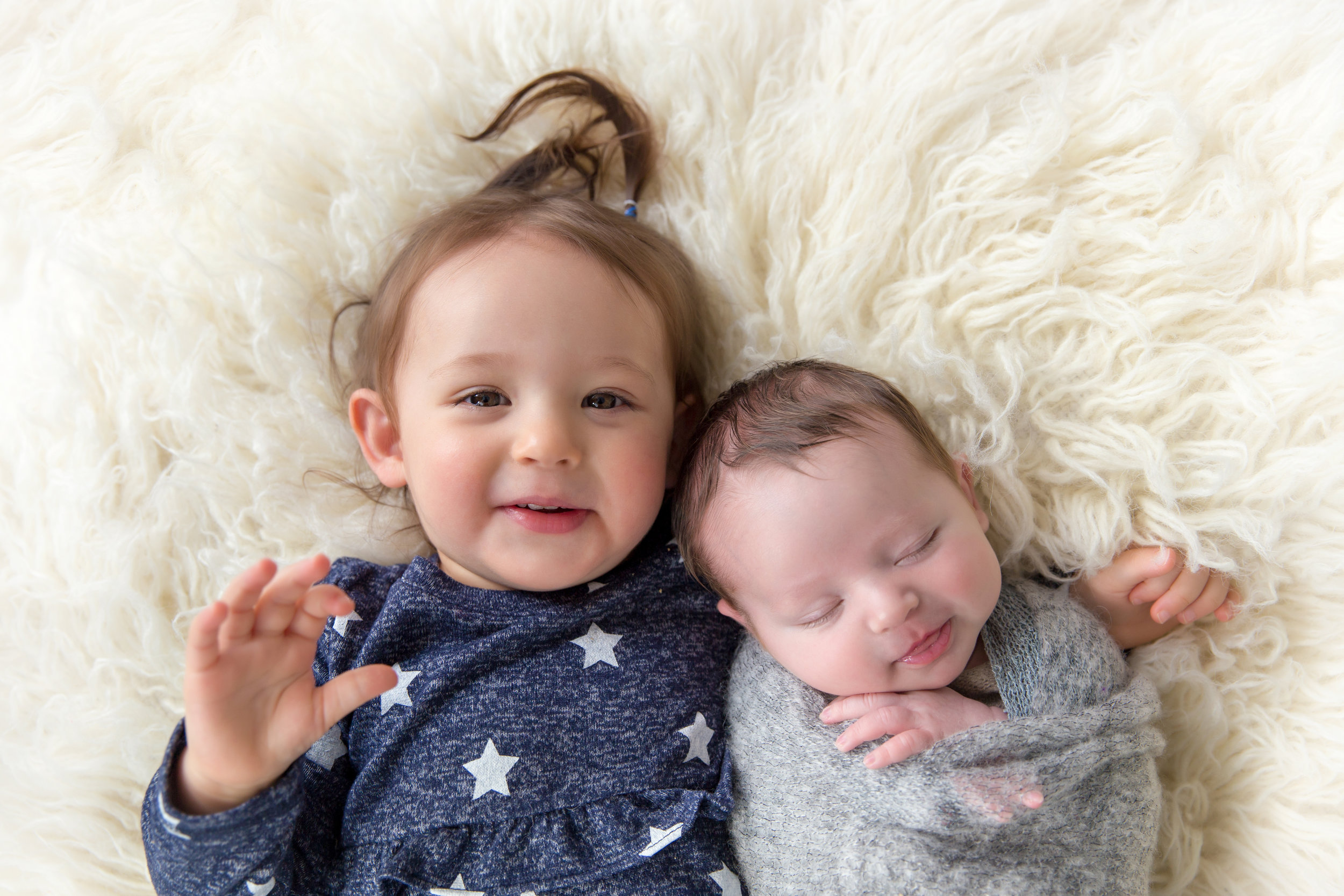 Siblings on a beanbag shot. Big sister is hugging her newborn baby brother. Calgary newborn photographer. Milashka Photography