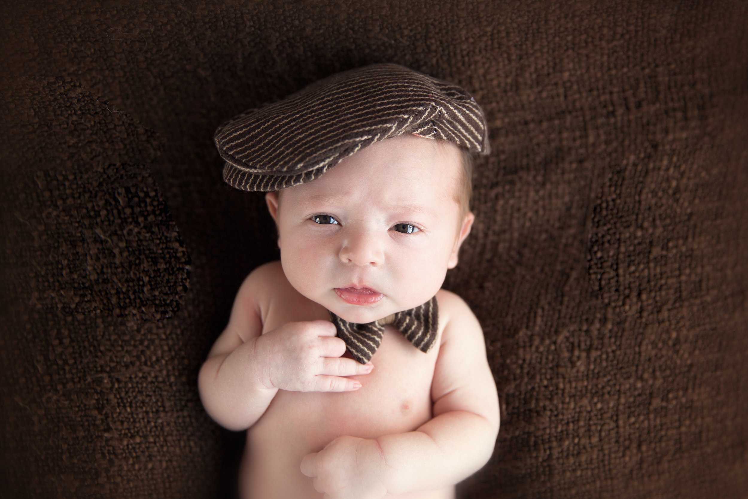 Newborn baby boy wearing old man hat and a bow-tie. Calgary Newborn photographer. Milashka Photography