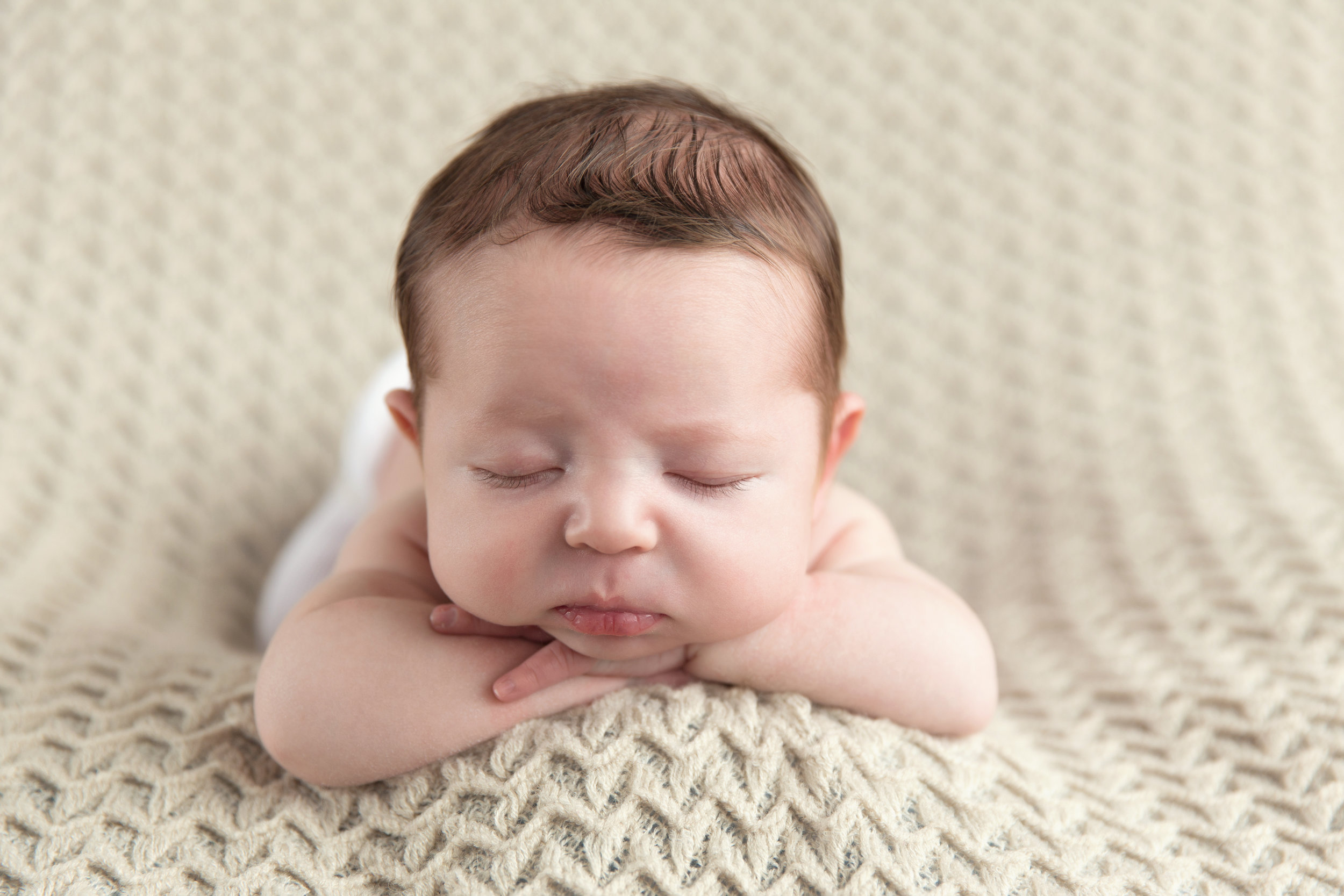 Newborn baby boy on a beanbag. Calgary Newborn Photographer. Milashka Photography