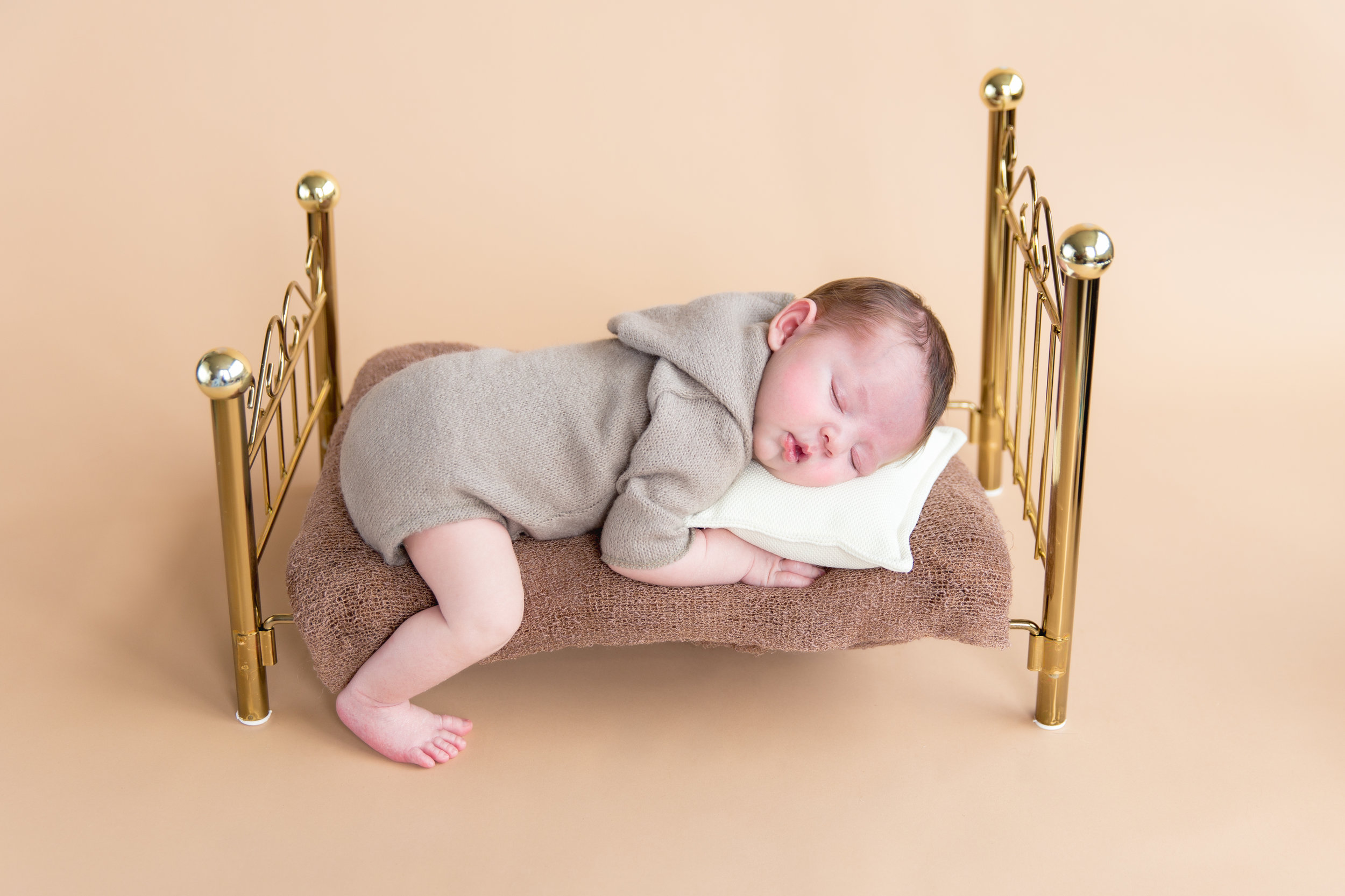 Newborn baby boy lying on a gold little antique bed. Calgary Newborn Photographer. Milashka Photography