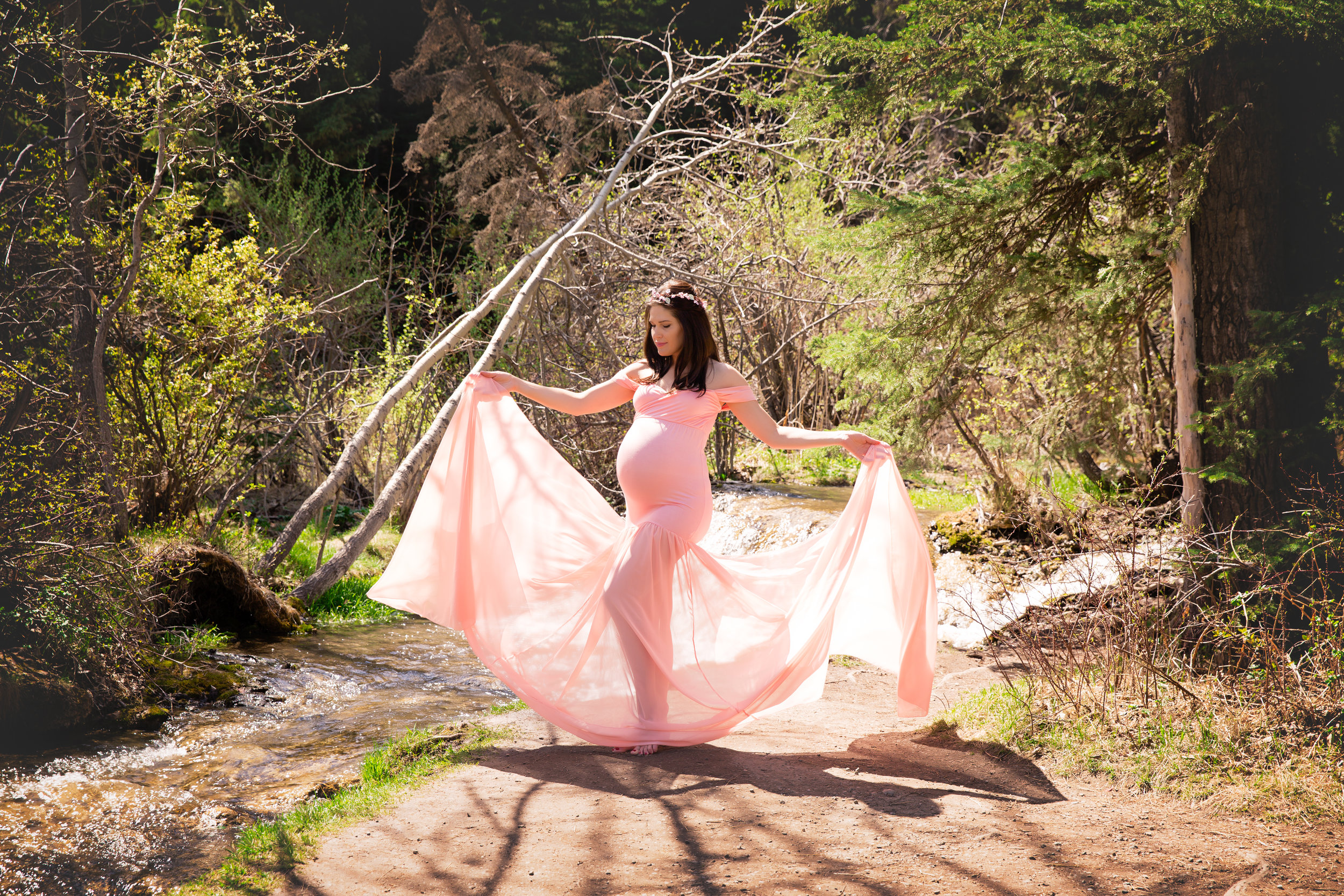Mother-to-be by the water in a coral-blush maternity gown. Calgary Maternity Photographer. Milashka Photography