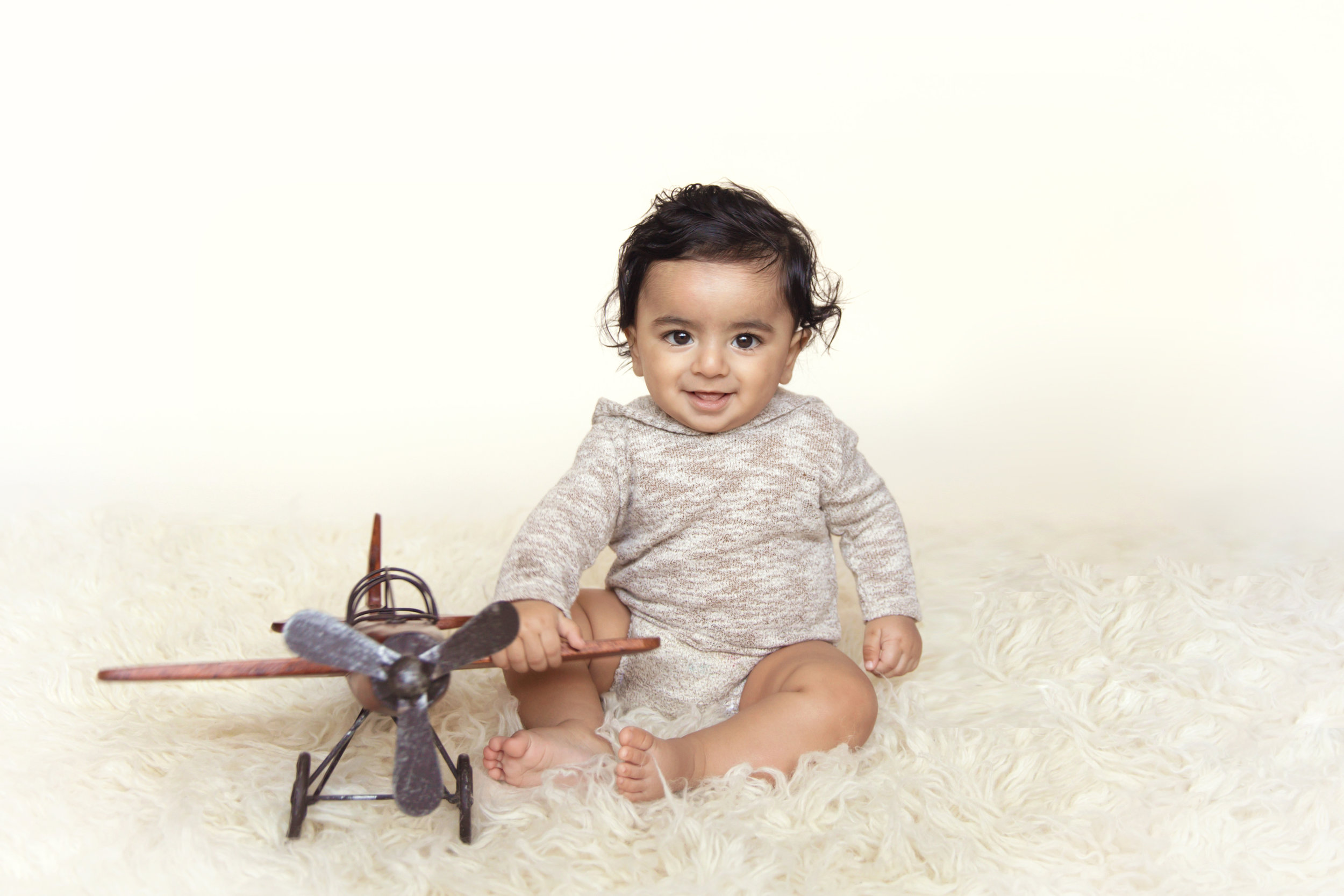 Baby boy sitting on a flokati rug with an airplane and smiling. Calgary baby photographer. Milashka Photography