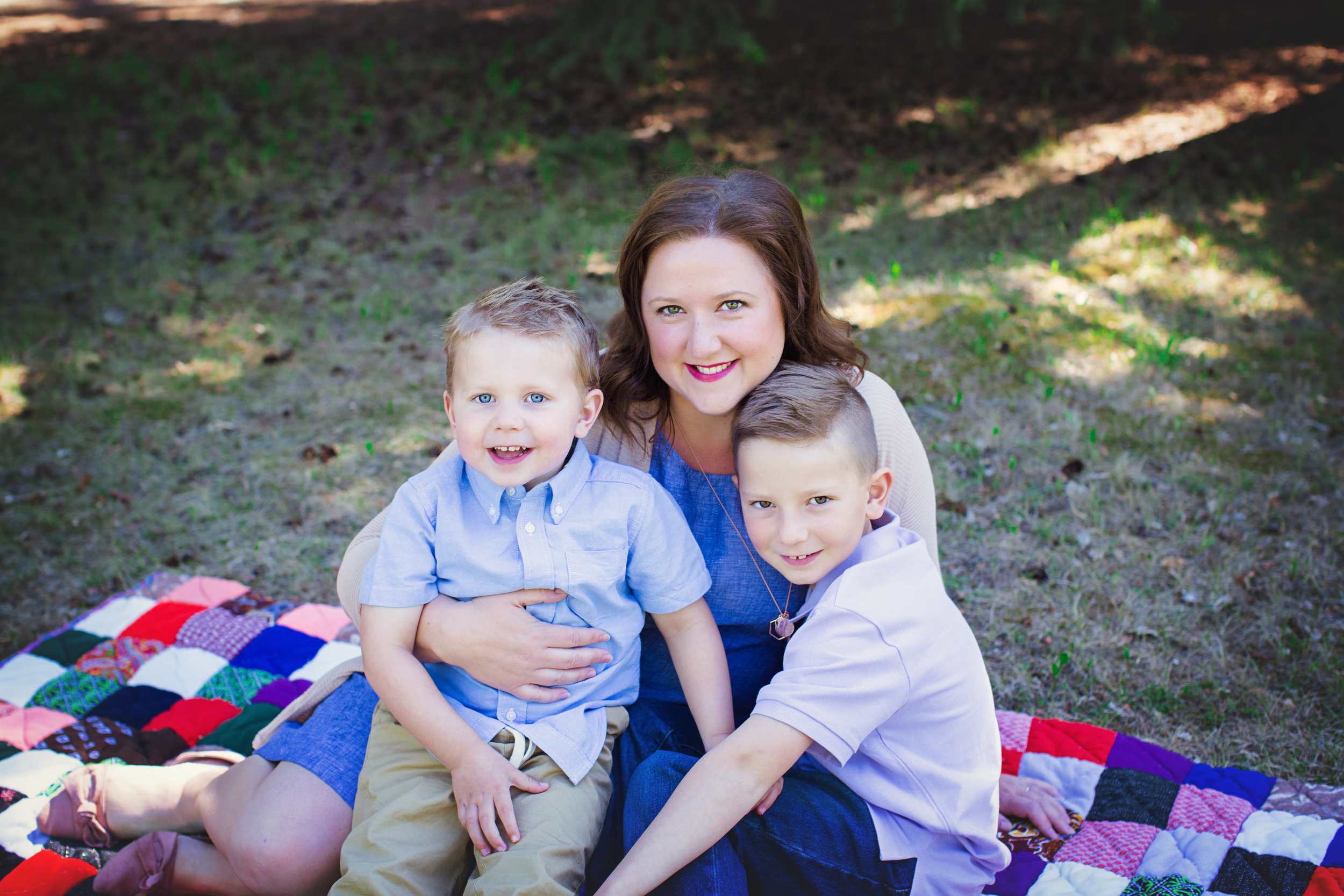 Mom and her 2 sons sitting on a blanket at the park. Calgary Family Photographer. Milashka Photography
