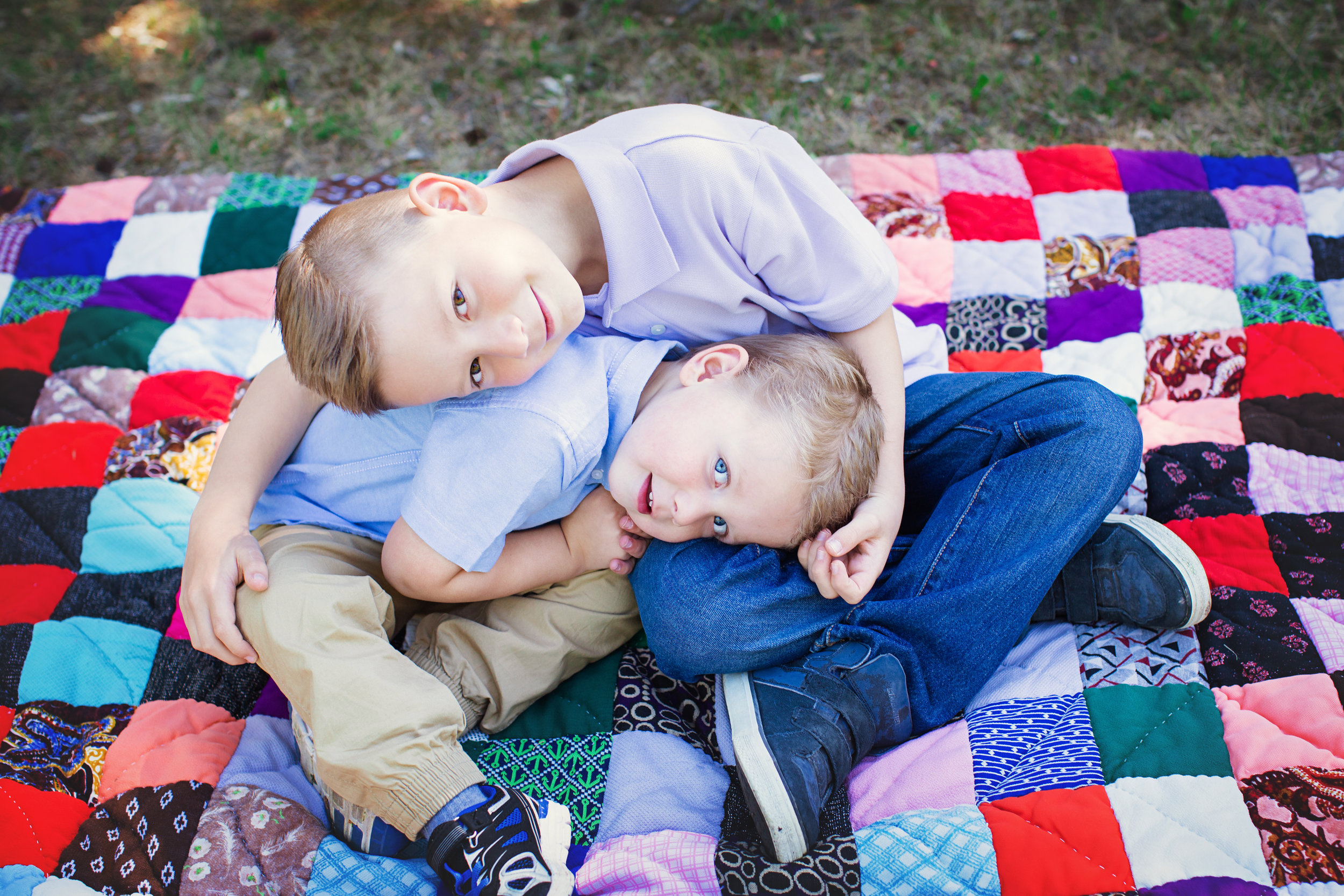 Brothers sitting on a blanket and hugging. Calgary Family photographer. Milashka Photography