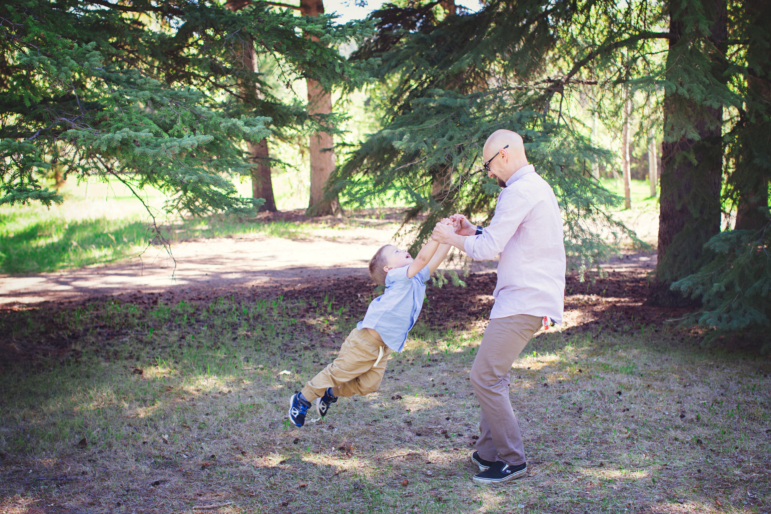 Dad and son playing in the park. Calgary Family photographer. Milashka Photography