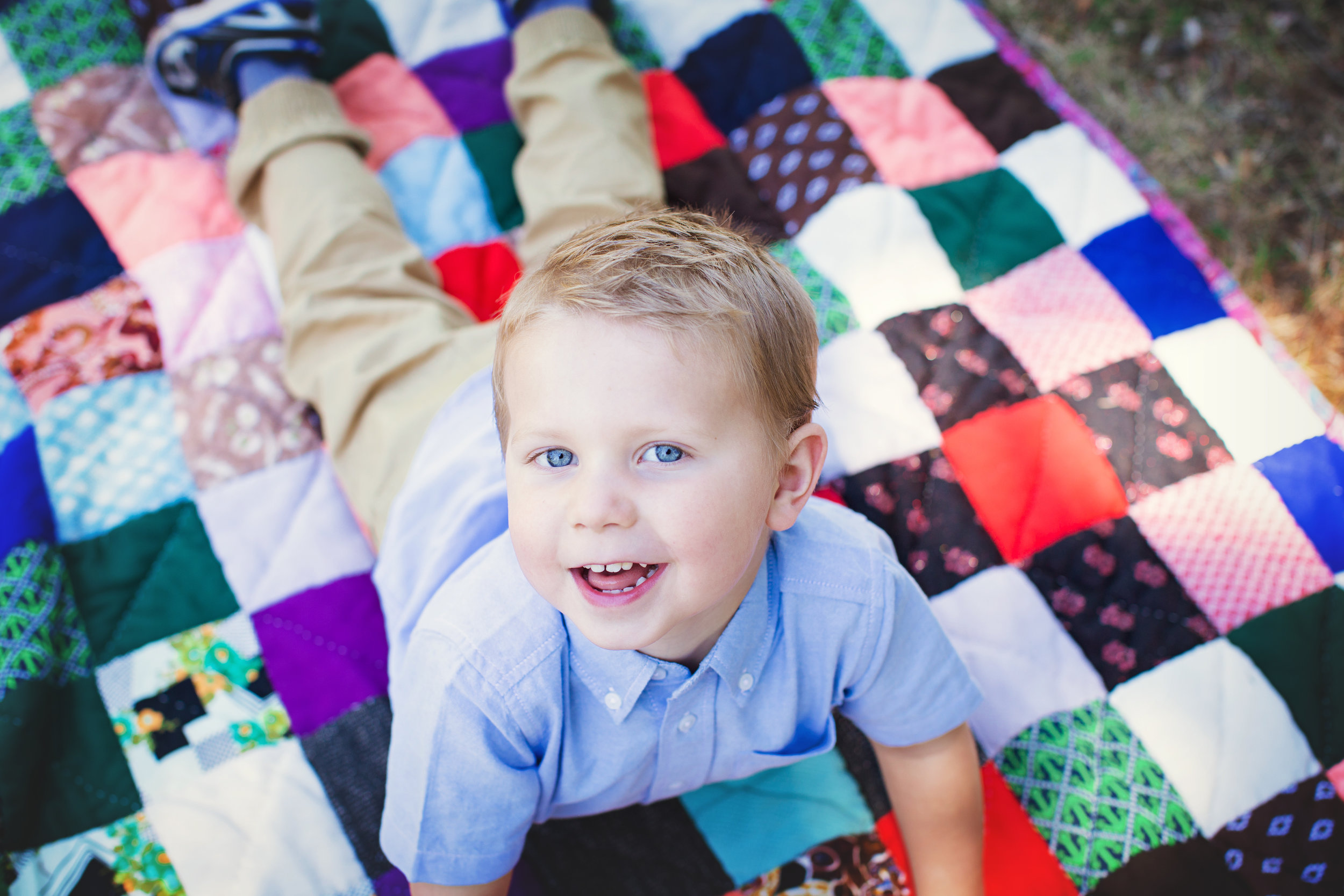 Boy with blue eyes lying down on a blanket and looking at the camera. Calgary family photographer. Milashka photography