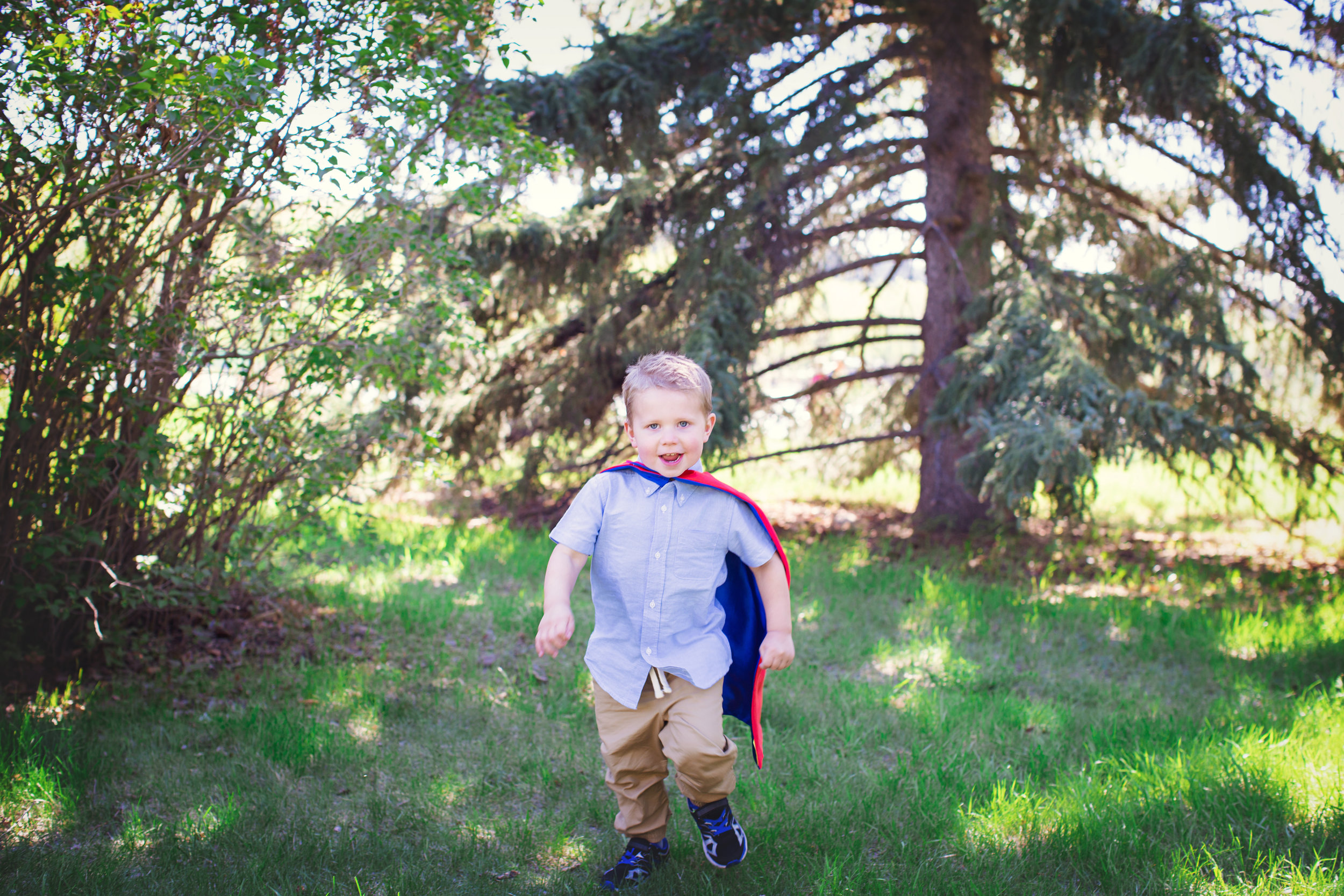Boy wearing a superhero cape running in the park. Calgary Family Photographer. Milashka Photography
