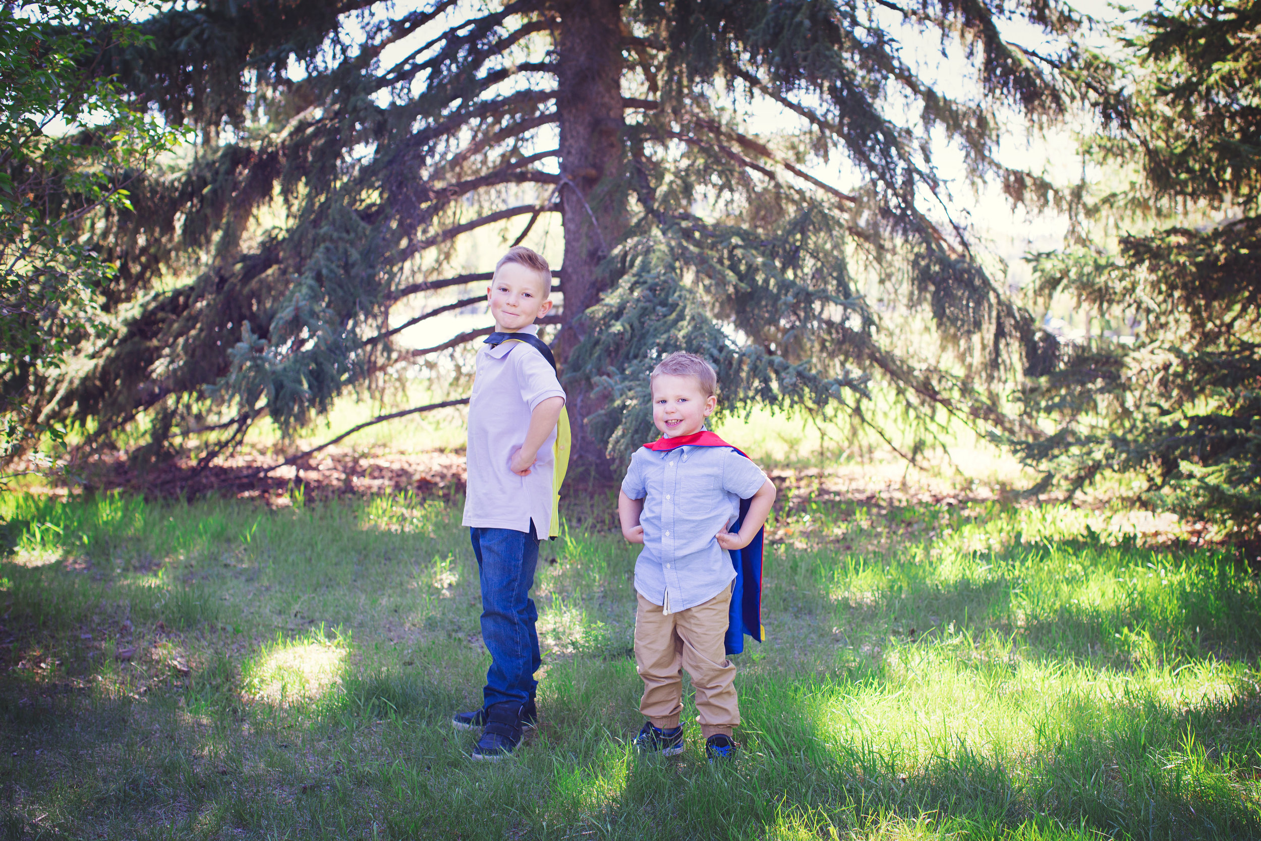 Brothers wearing superhero capes and posing. Baker's park. Calgary family photographer. Milashka Photography