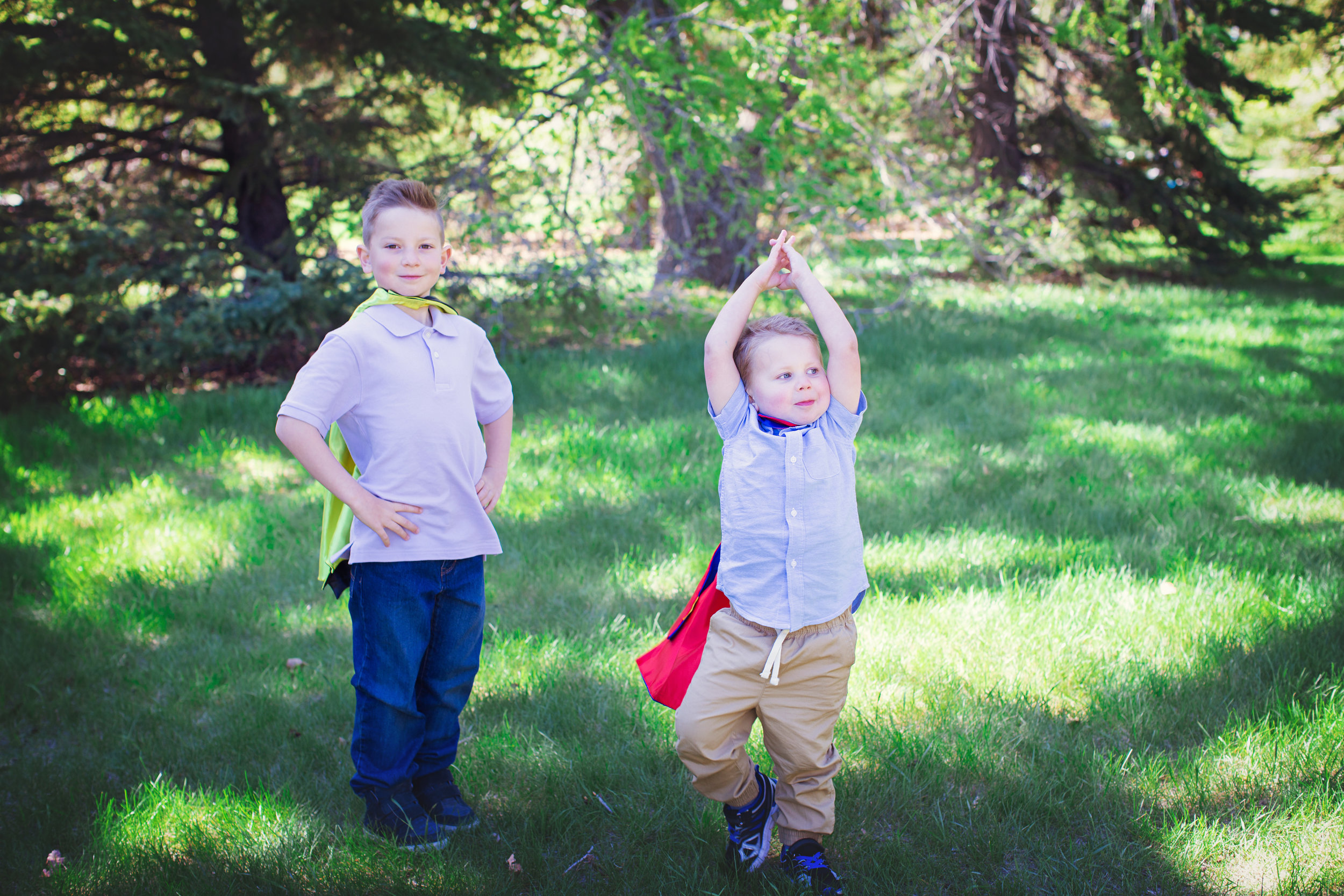 Brothers are wearing superhero capes and posing. Baker's park in Calgary. Calgary family photographer. Milashka Photography