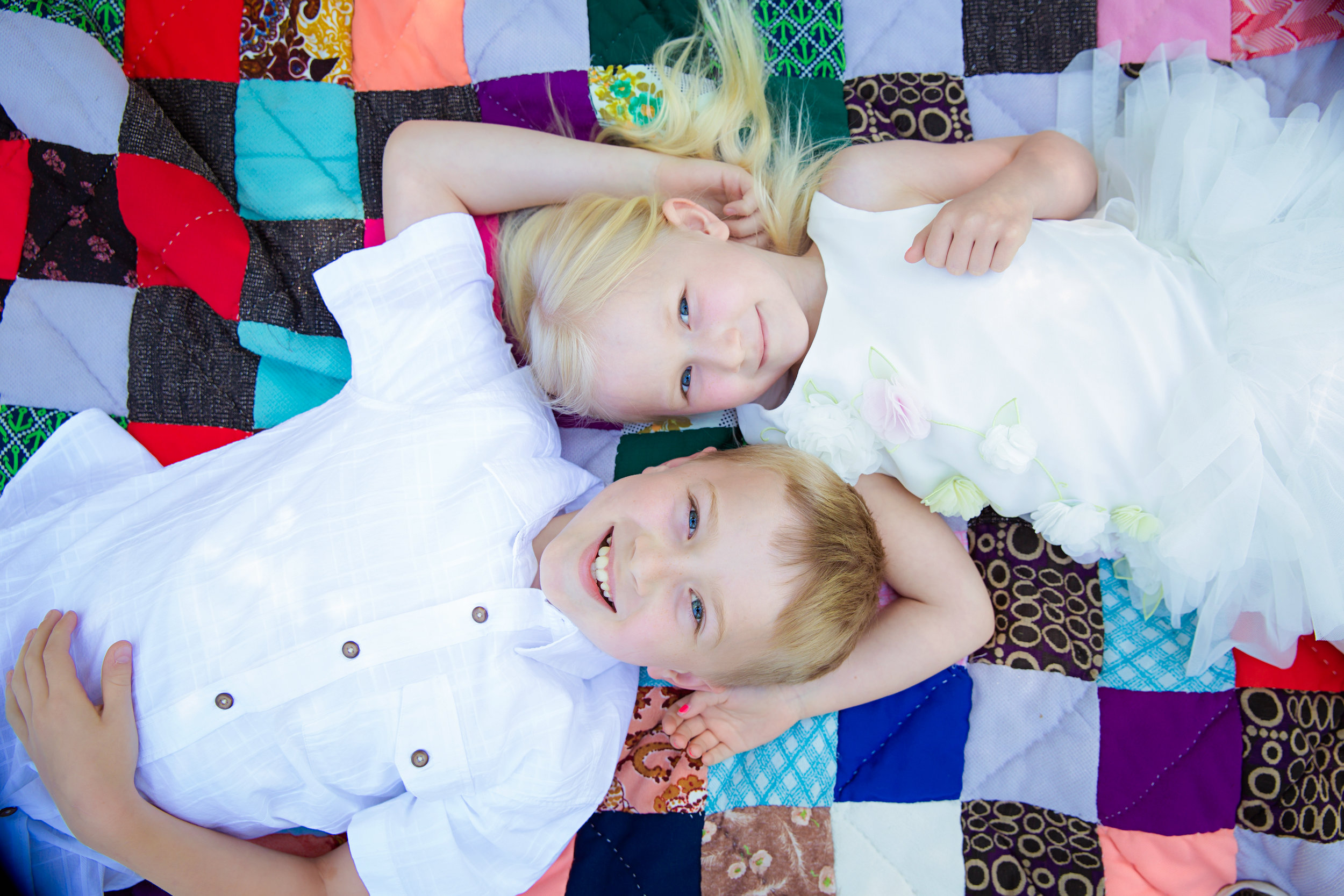 Siblings lying down on a blanket and looking at the camera. Calgary children photographer. Milashka Photography