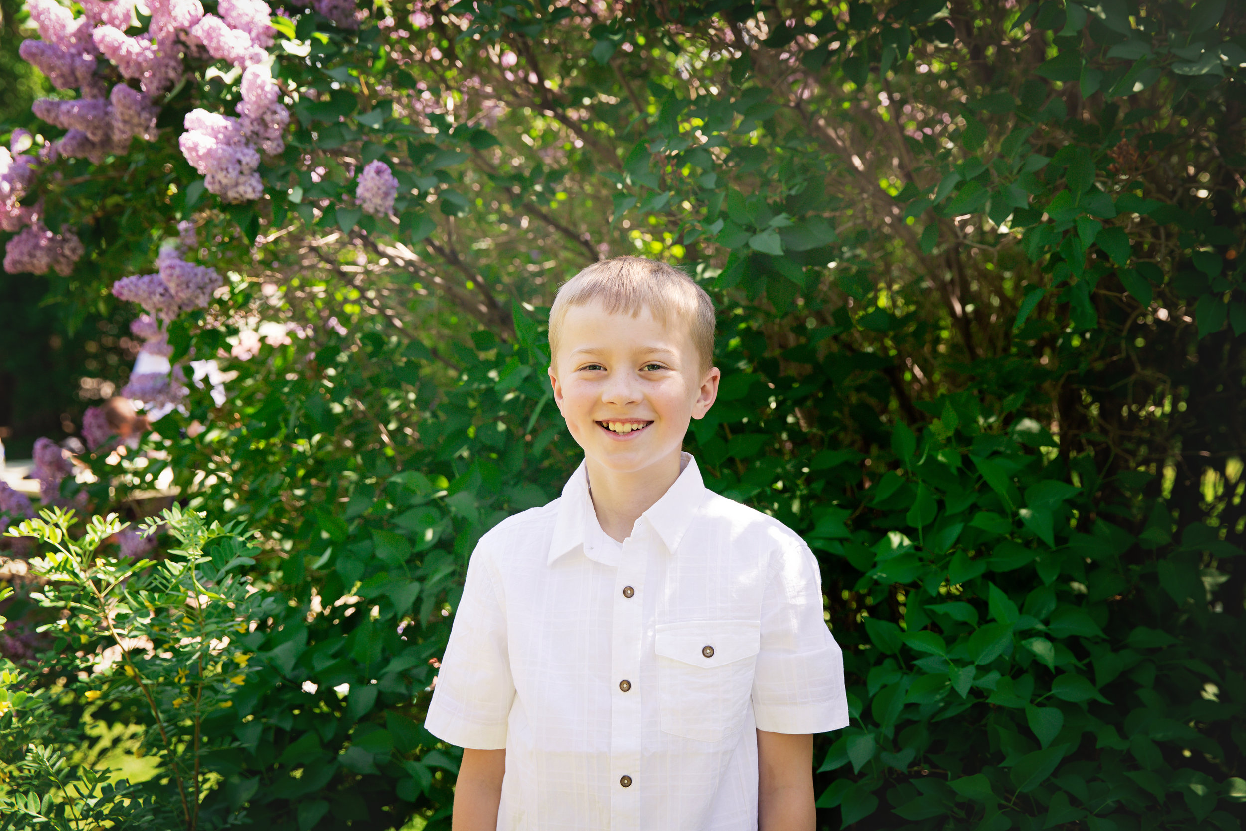 Boy standing in front of the blooming lilac tree. Calgary Photographer. Milashka Photography