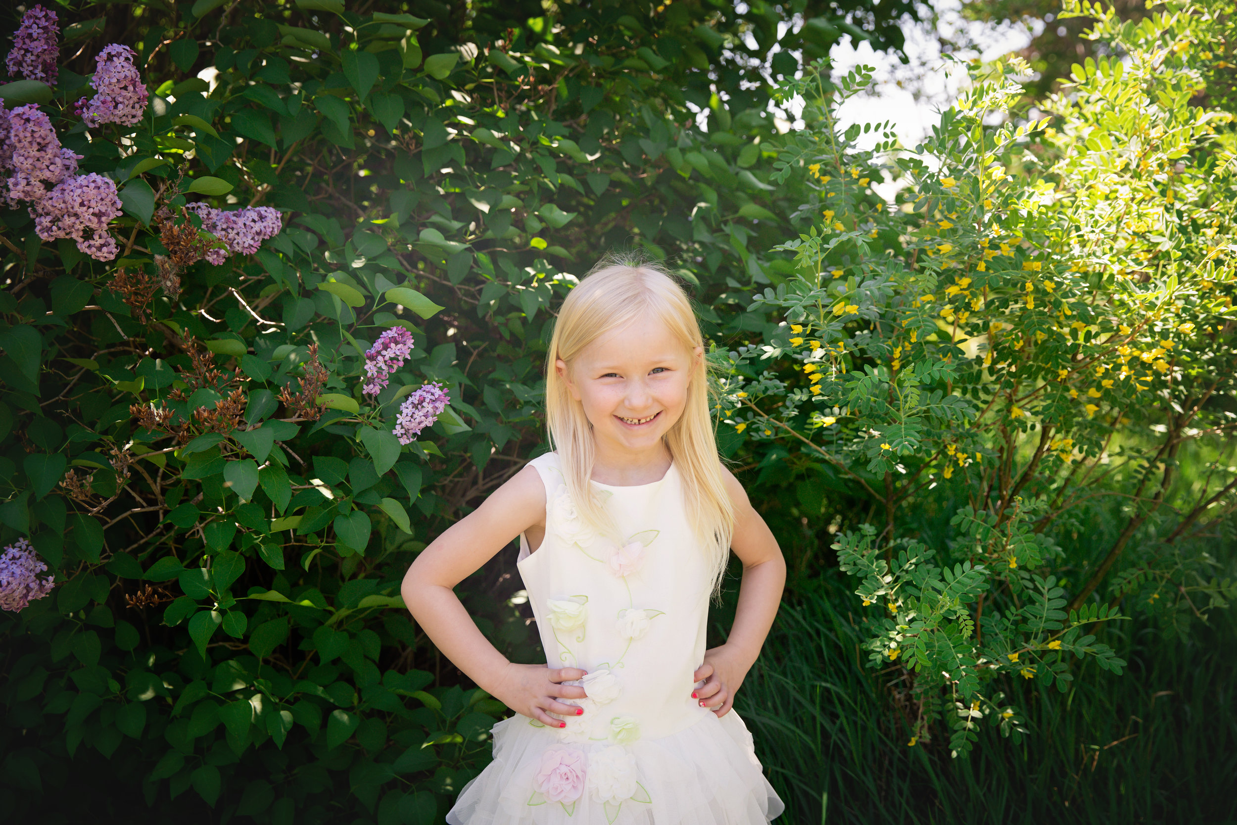 Girl is standing in front of the lilac tree and smiling. Rotary Park. Calgary Child Photographer. Milashka Photography