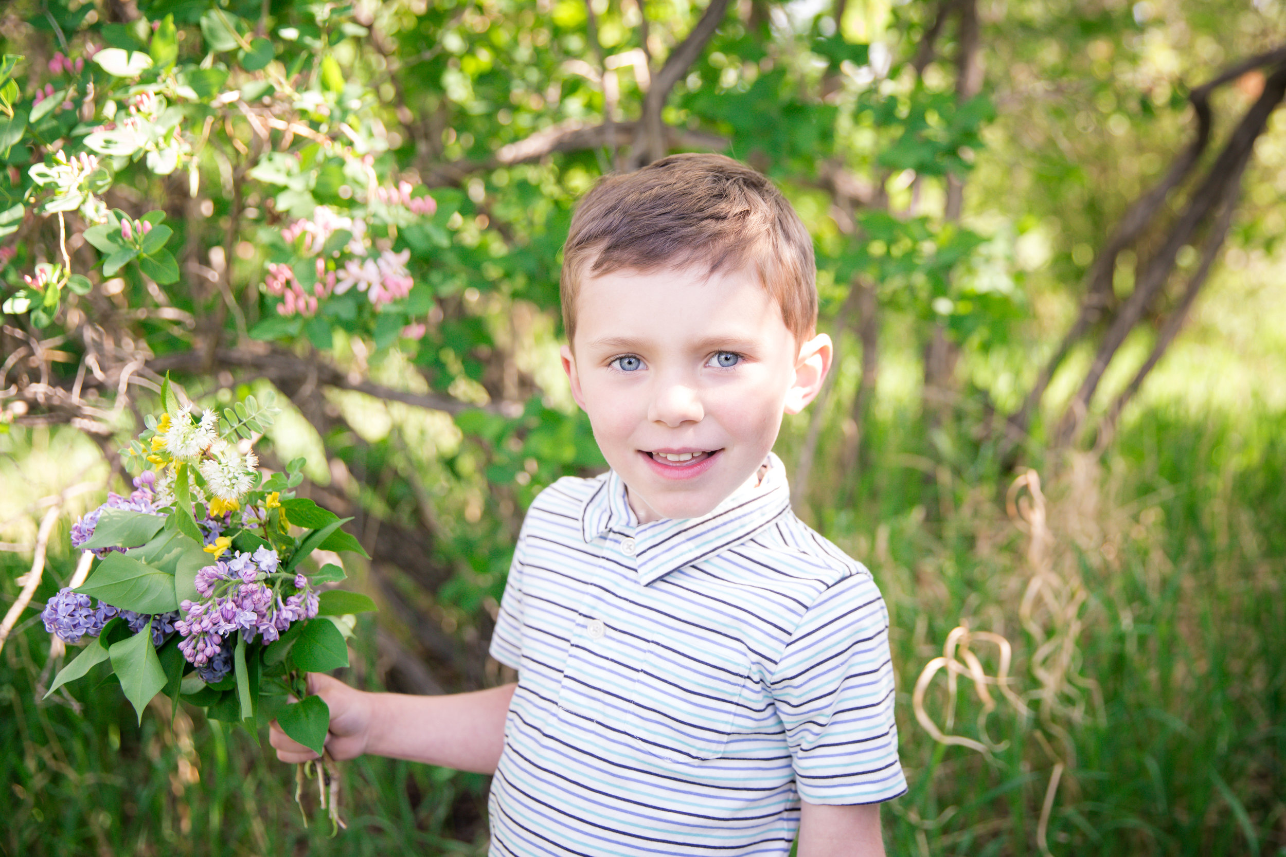 Boy standing by lilac tree and smiling. Calgary child photographer. Milashka Photography
