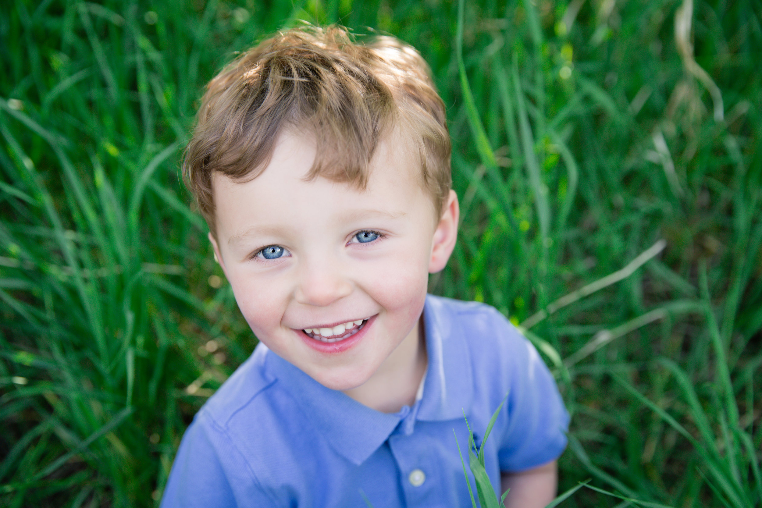 Boy in a blue shirt, smiling and looking at the camera. Calgary child photographer. Milashka Photography