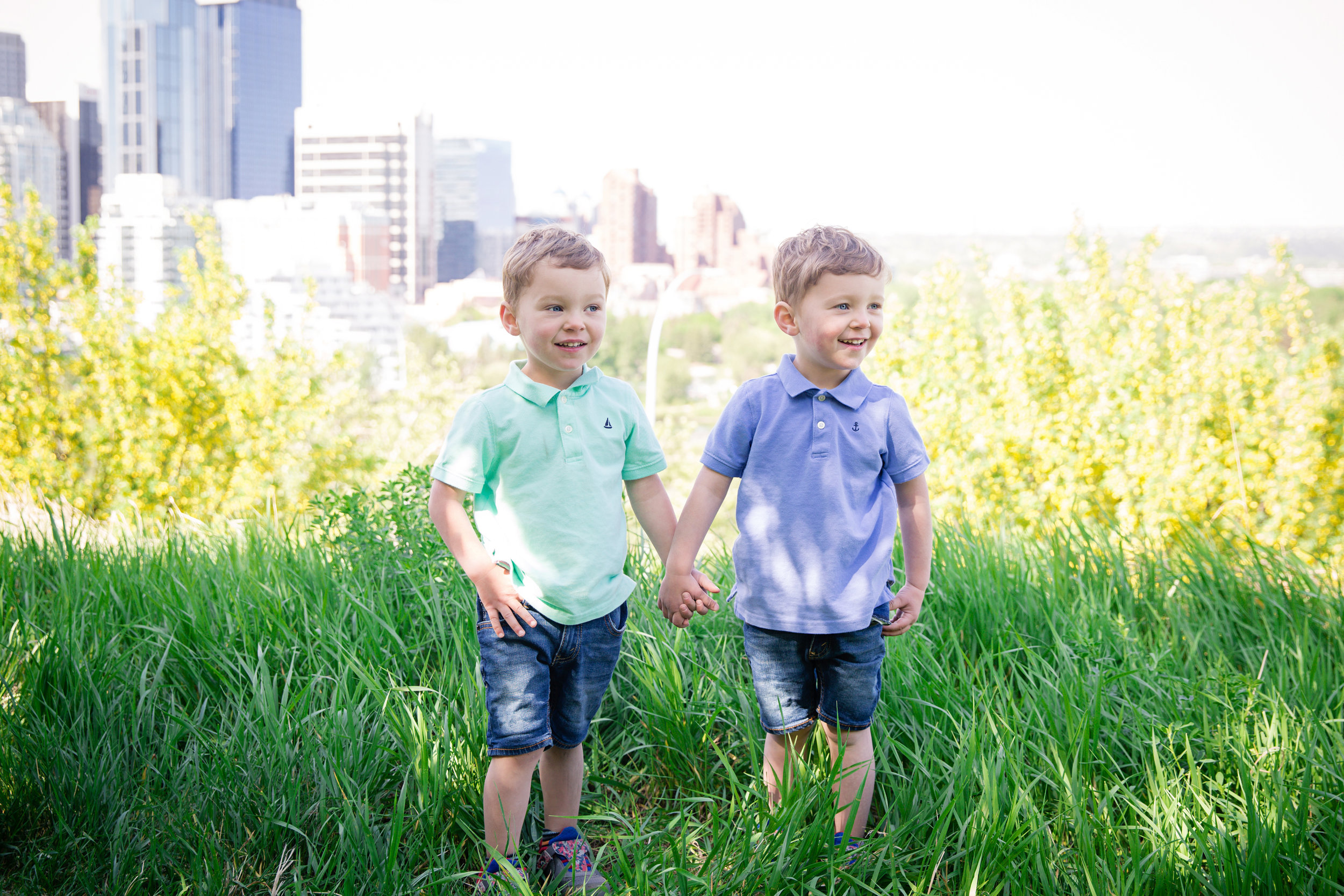 Twin boys holding hands. Calgary downtown background in Rotary park. Calgary Family Photographer. Miashka Photography