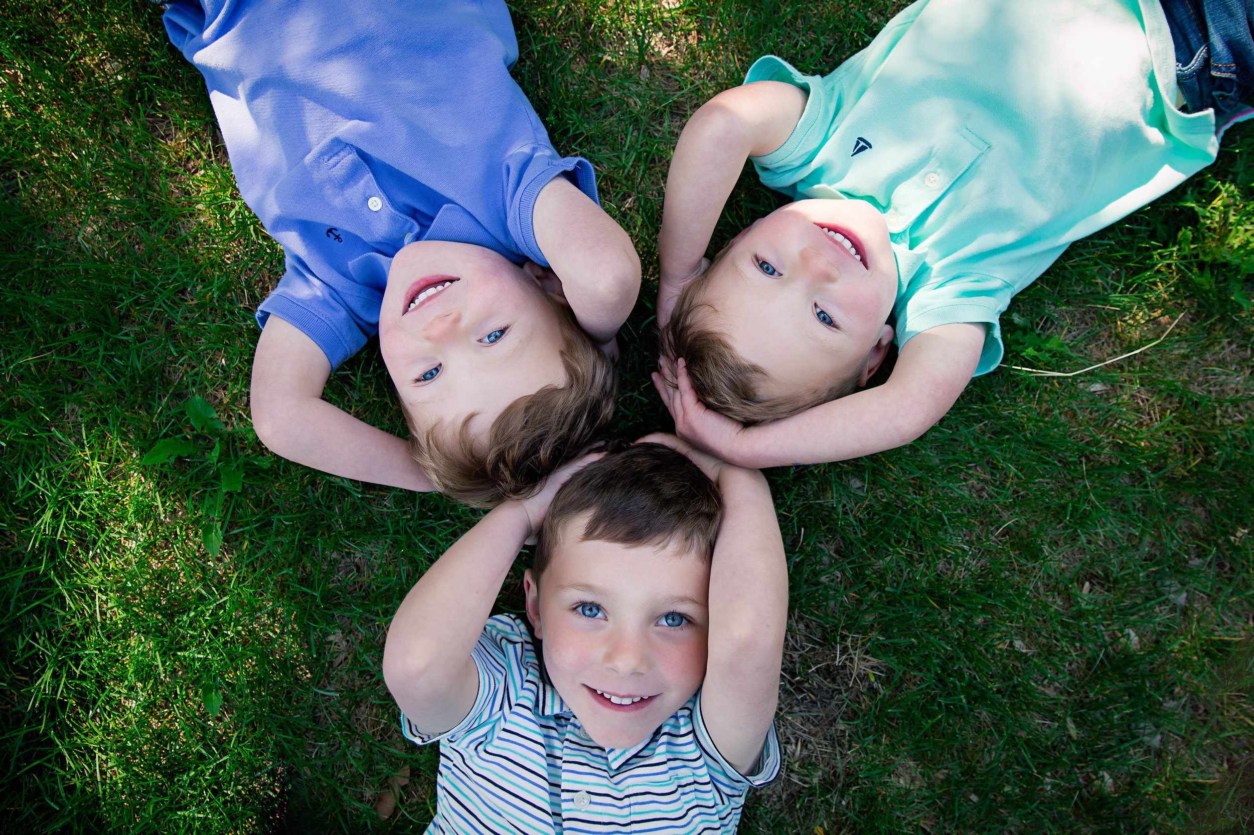 3 brothers lying on the grass head to head and smiling. Calgary child Photographer. Milashka photography