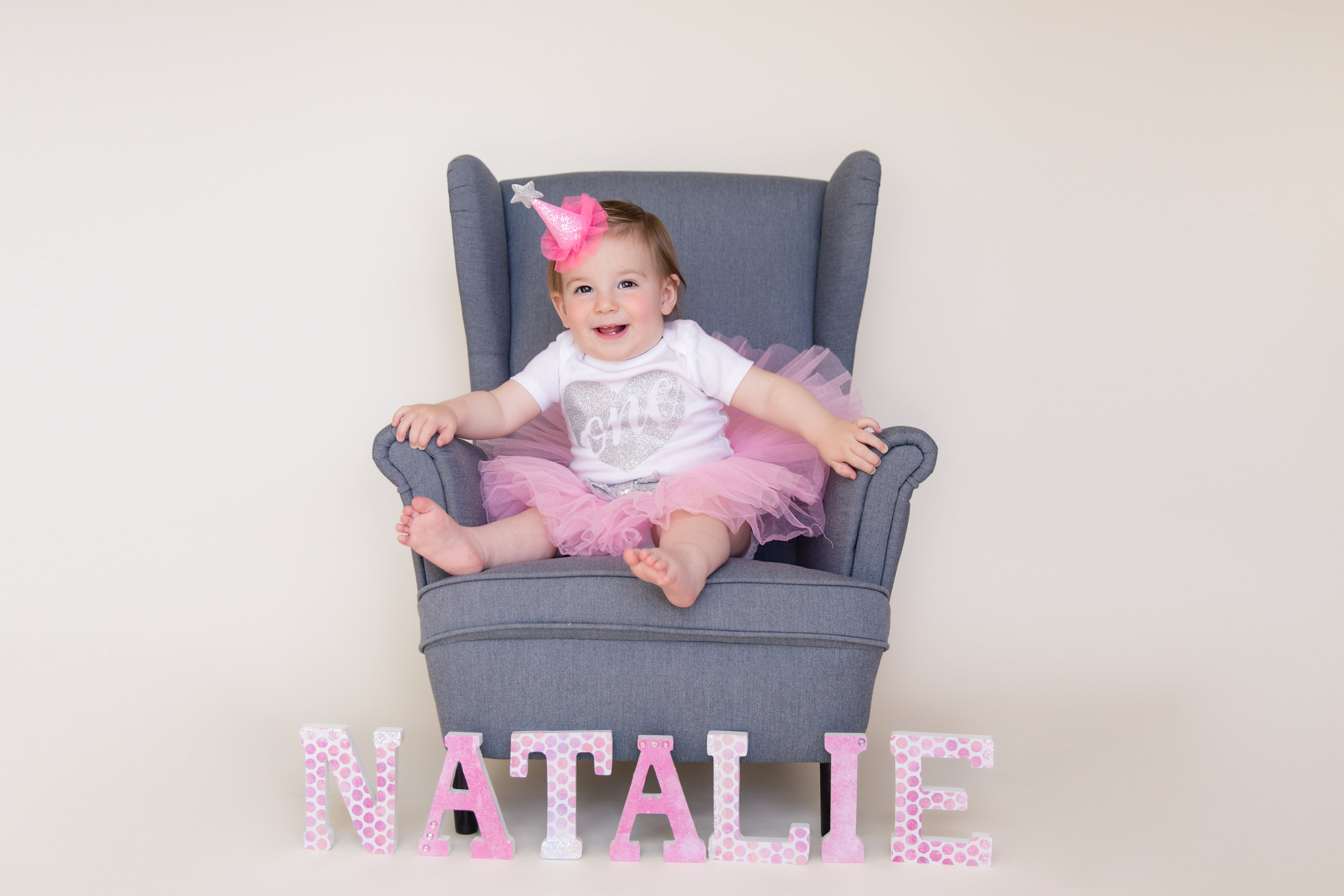 "Baby girl sitting on a chair wearing a tutu and a onesie that says ""one"". Calgary baby photographer. Milashka Photography."