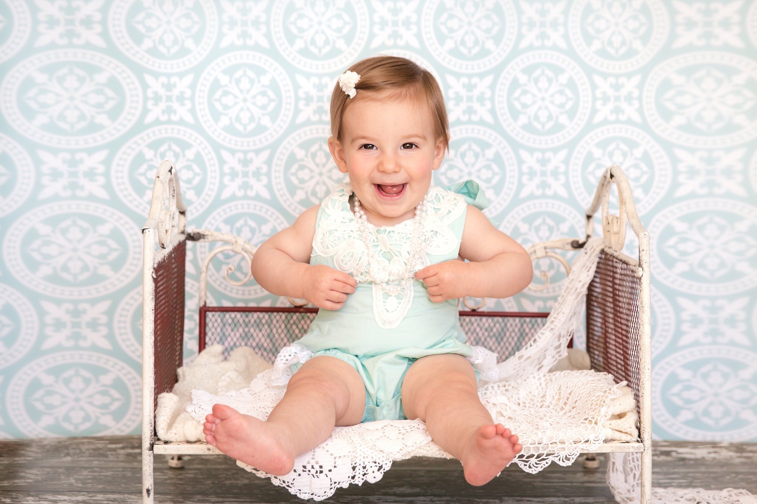 Baby girl sitting on an antique bed wearing cute outfit, pearls and smiling. Calgary baby photographer. Milashka Photography.