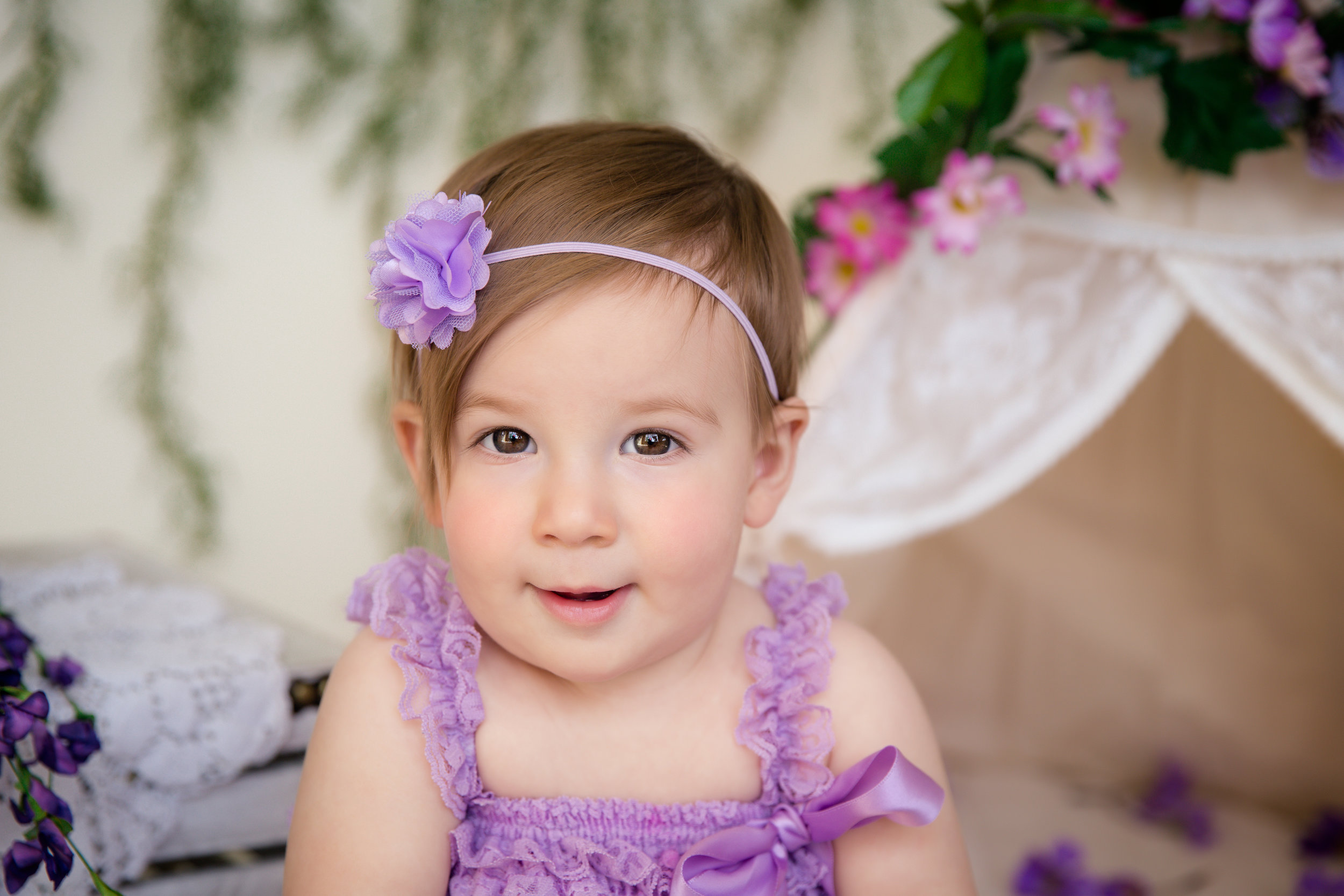 Beautiful baby girl, wearing a purple romper and looking right at the camera. Calgary baby photographer. Milashka Photography