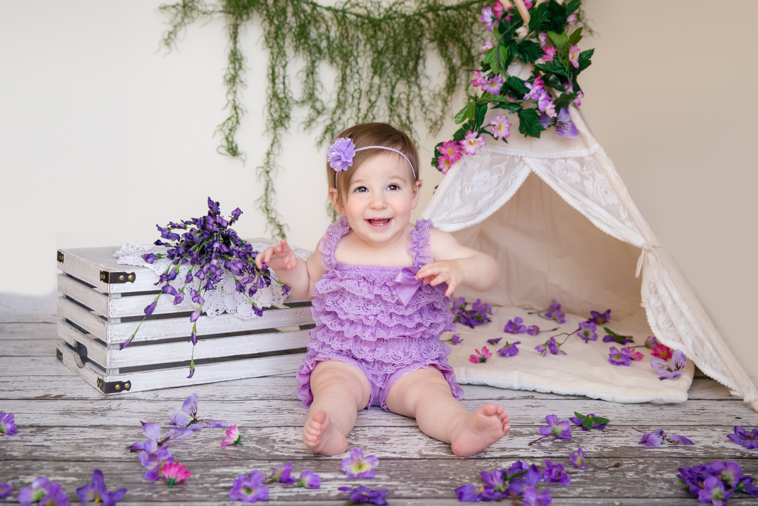 Baby girl wearing a cute violet romper sitting in front of the tipi and surrounded by flowers. Calgary baby photographer. Milashka Photography.