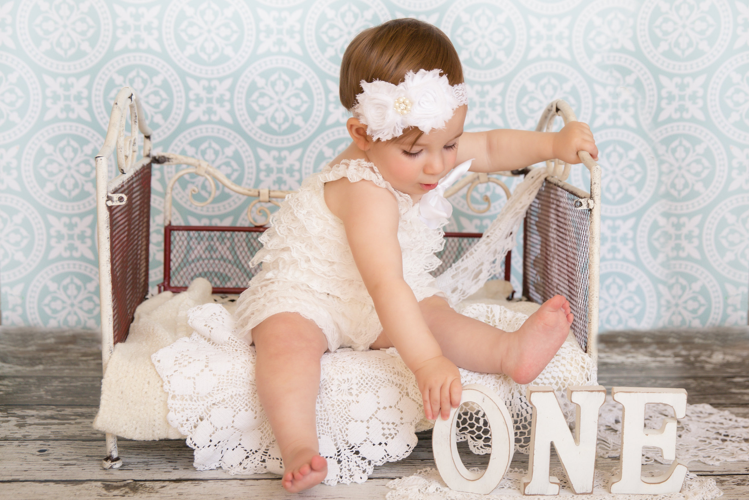 "Little girl is wearing a white romper, sitting on an antique bed and reaching out for letter ""O"" from the word ""ONE"". Calgary baby photographer. Milashka Photography"