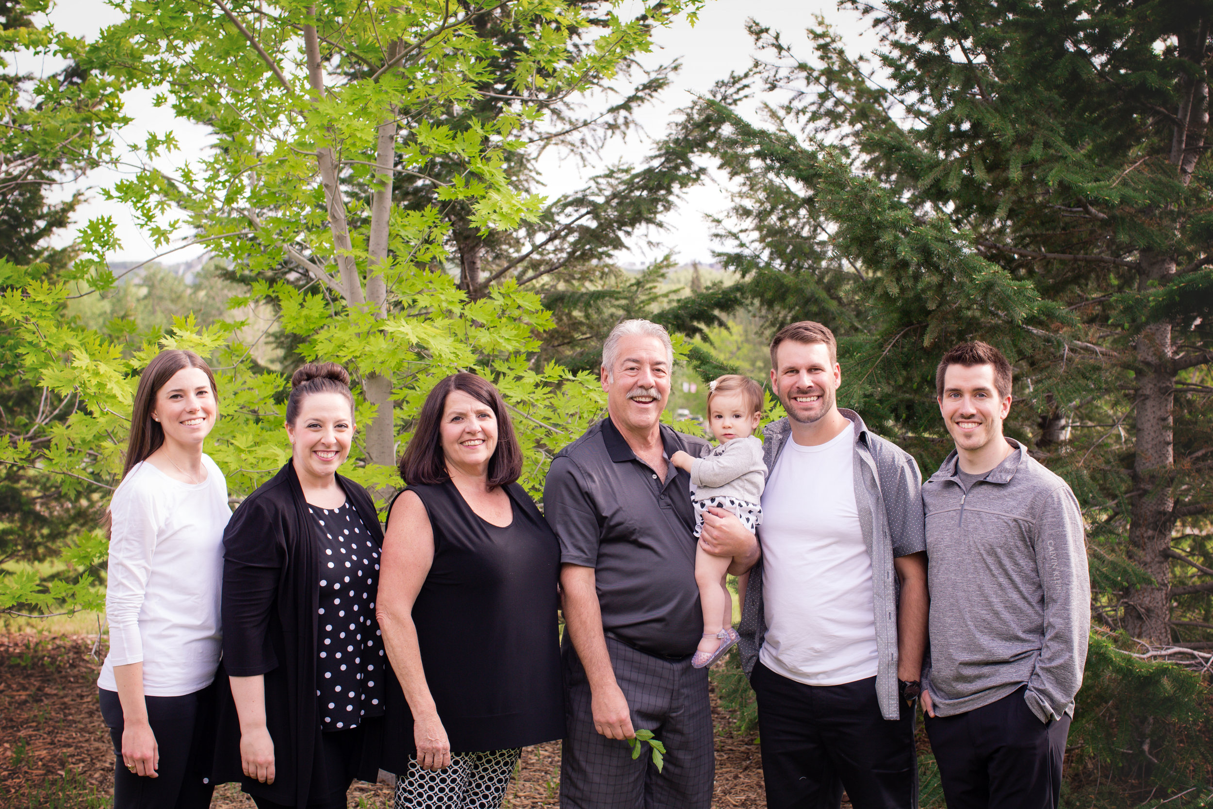 Family photoshoot at Baker's park. We have all the ladies on one side and all the guys on the other side, looking at the camera and smiling. Alberta family photographer. Milashka photography
