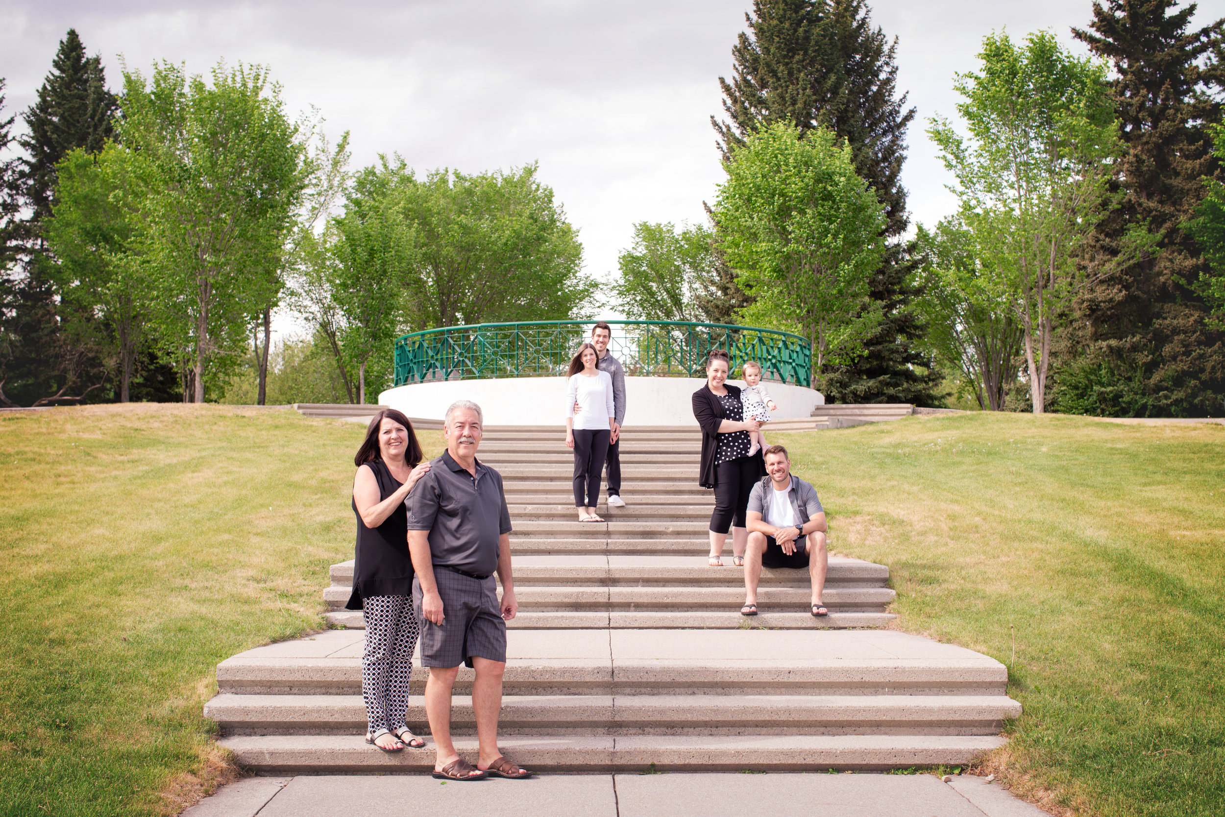Family of 7 divided by inner smaller families standing on the stairs in Baker's park. Calgary photographer. Milashka Photography